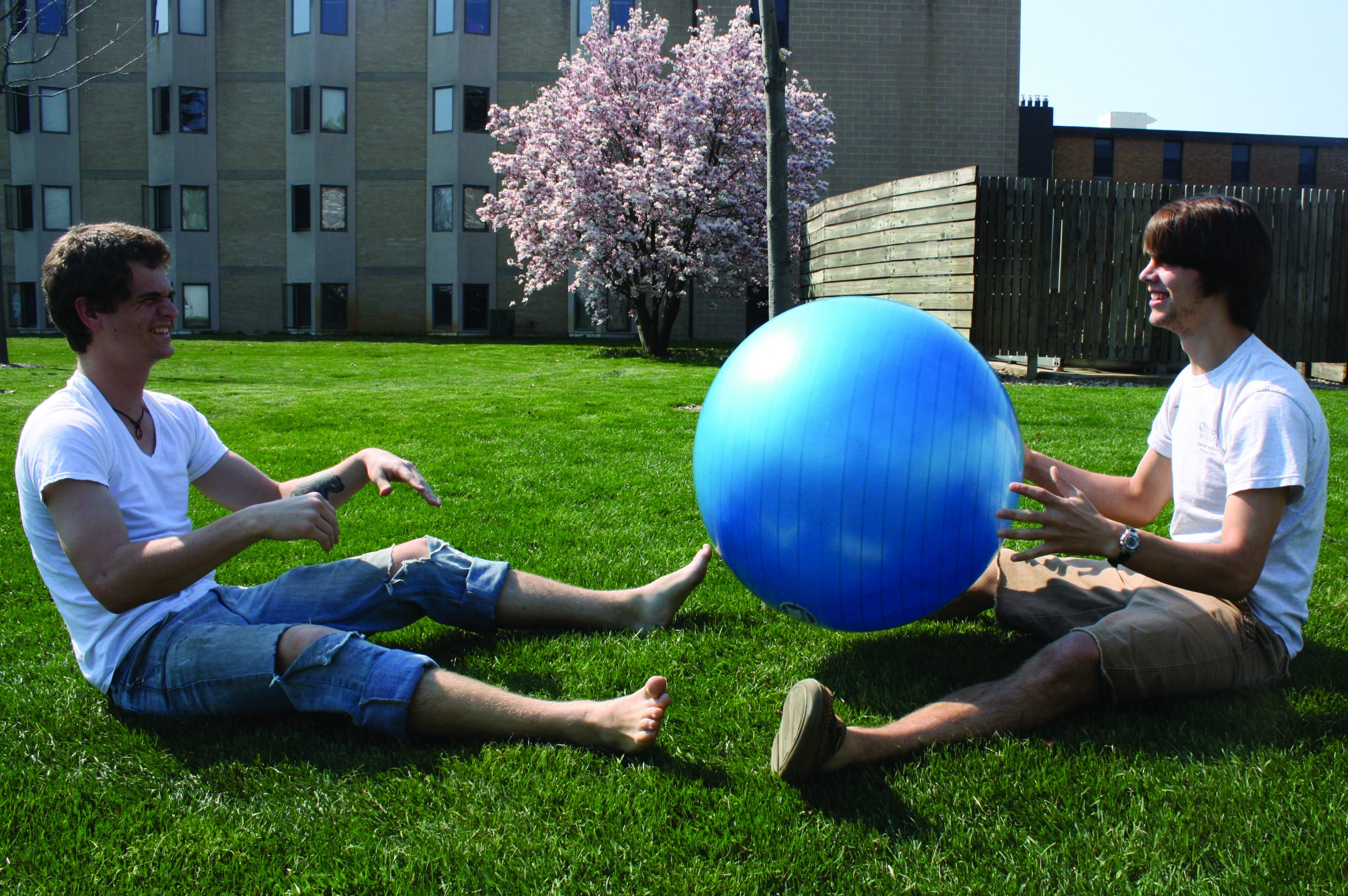 Two students play with a bouncy ball on the KMY lawn