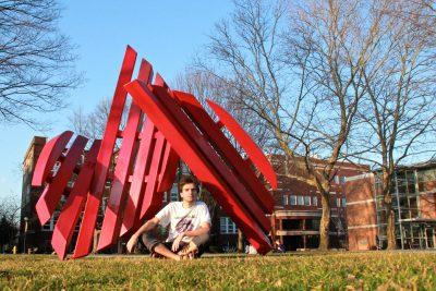 Daniel Penner sits under the Broken Shield sculpture