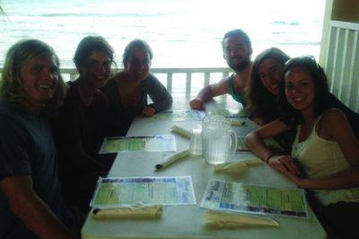 Sara Alvarez, her five friends, and her grandmother sit in a Puerto Rican restaurant booth with the ocean in the background