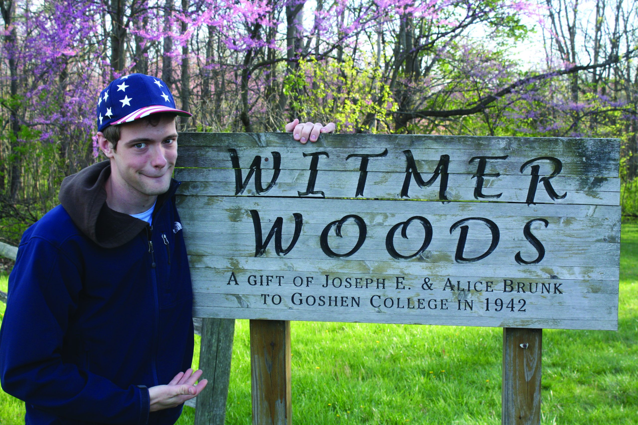 Daniel Penner stands next to a Witmer Woods sign