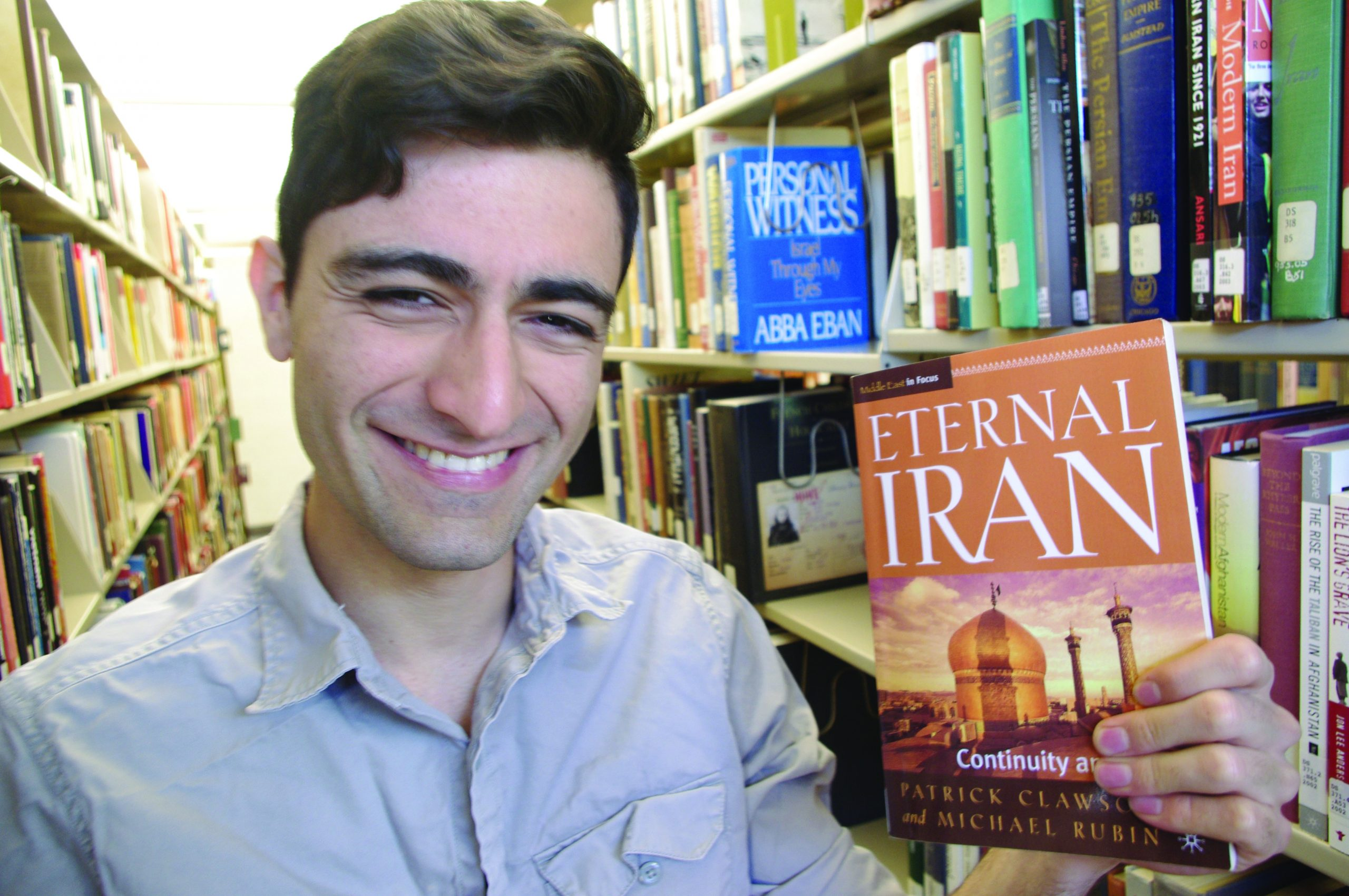 Portrait of Mohammed Rasouplipor with book on Iran