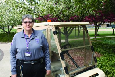 Tammy Anderson stands in front of a golf cart in her campus security uniform