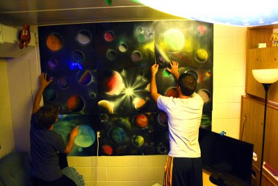 Aaron Bontrager and Jordan Weaver hang up a poster of outer space in their dorm room