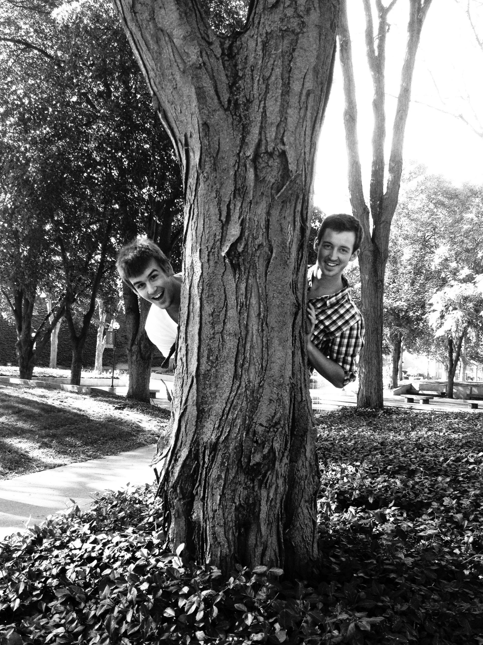 John Miller and Jonny Hersh stick their heads out from behind a tree for a picture