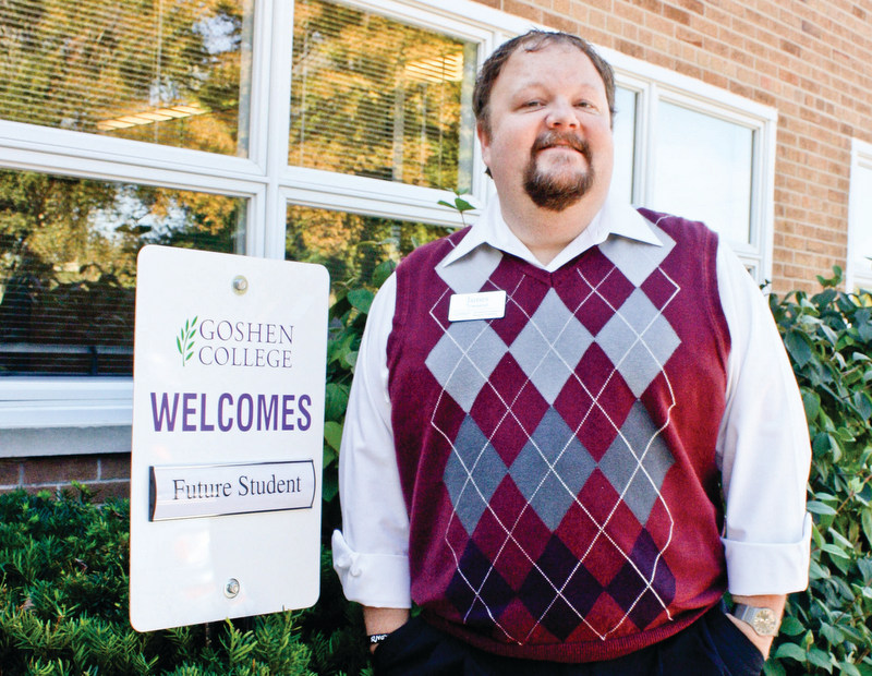 """James Townsend stands next to a """"Goshen College Welcomes Future Students"""" parking sign"""