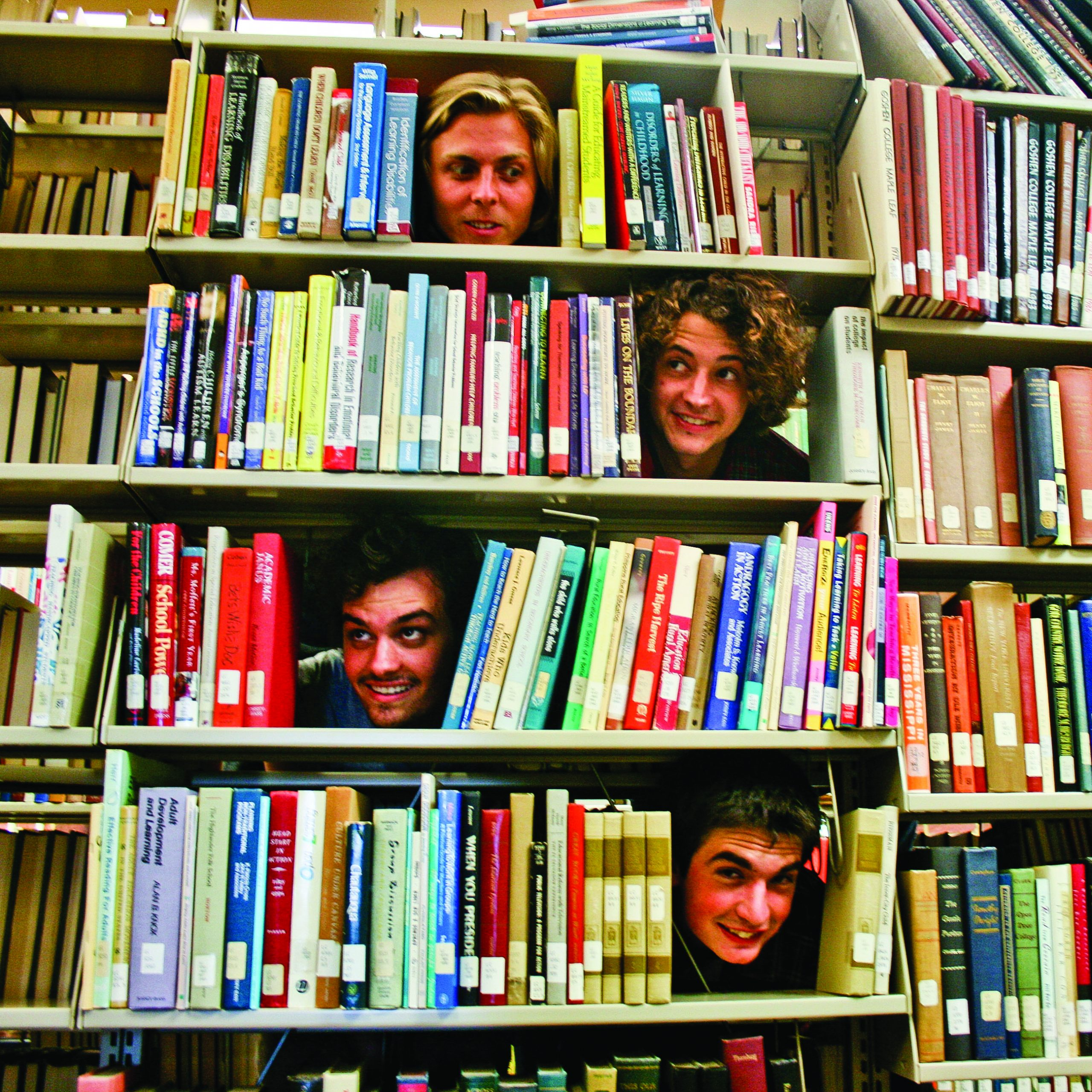 Kansas Bible Company members Charlie Frederick, Nate Klink, Jacob Martin and Jeff Yoder pose for a funny picture, sticking their heads through open spaces in bookshelves in the Good Library