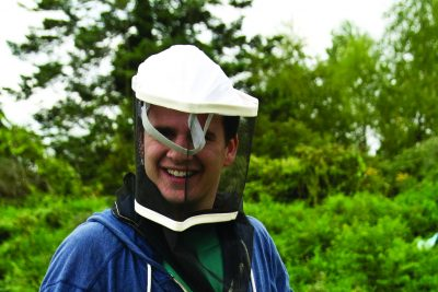Peter Martin wears beekeeping gear and holds a section of a bee hive
