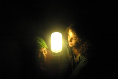 Natalie Hartman and Emily Kraybill pose with half of their faces illuminated by the ghost's light in Umble Center