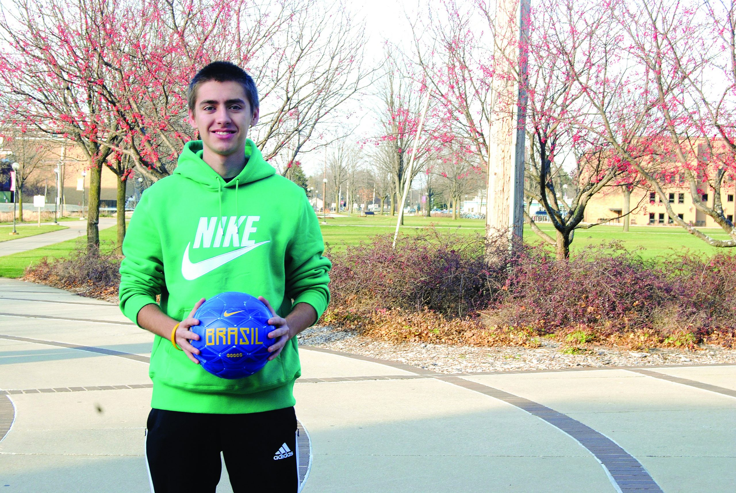 """Diego Zago wears a neon green """"Nike"""" hoodie and holds a soccer ball on the Goshen College campus"""