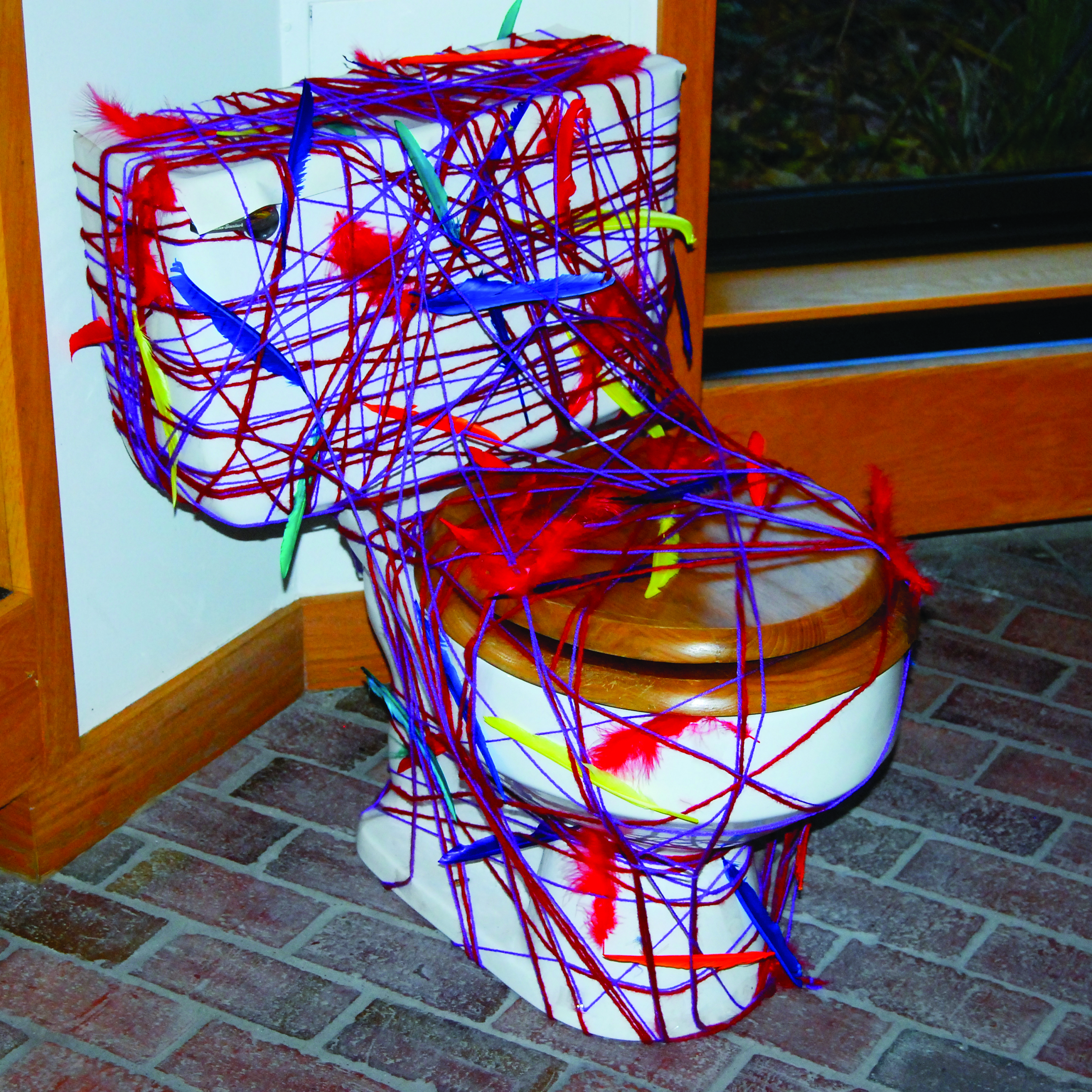 A toilet covered in brightly colored yarn and feathers