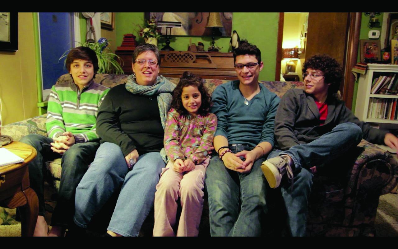 Jillian De Moya sits on the couch of her family home alongside her four children