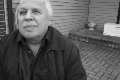 Black and white image of Marvin Graber sitting on his porch