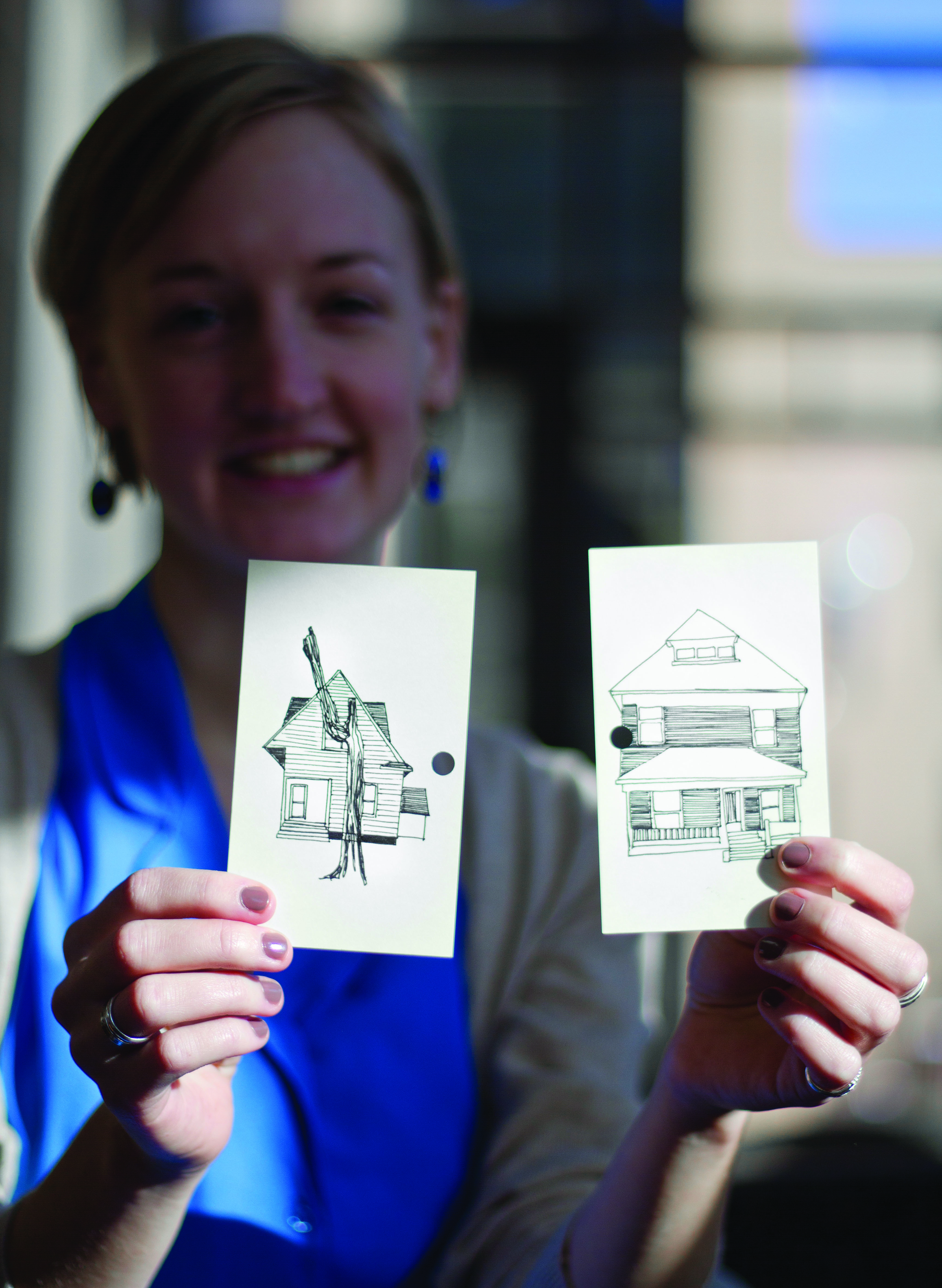 Abbie Miller holds up her drawings of houses on 8th Street
