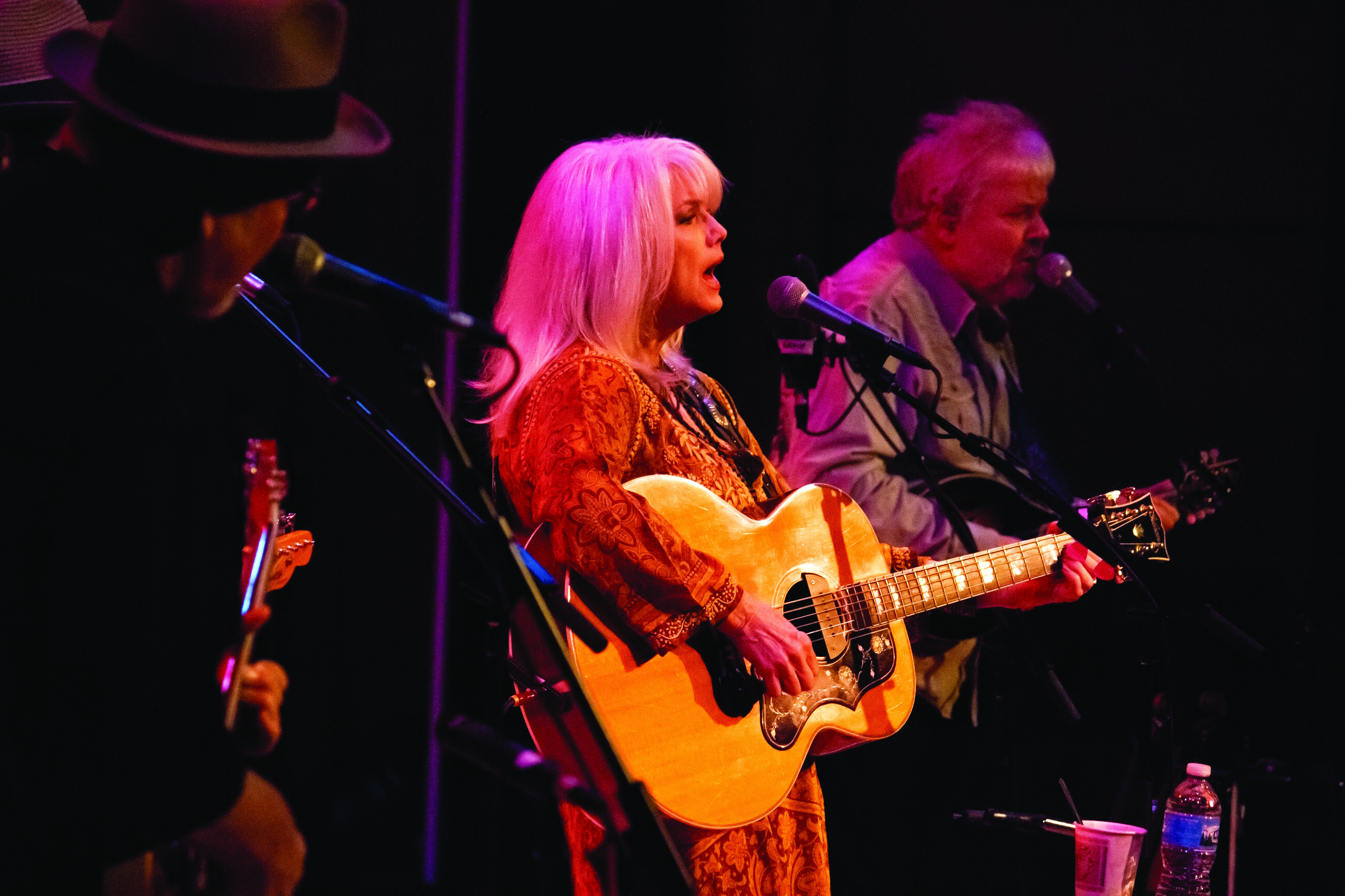 Emmylou Harris plays guitar and sings into a microphone in Sauder Concert Hall