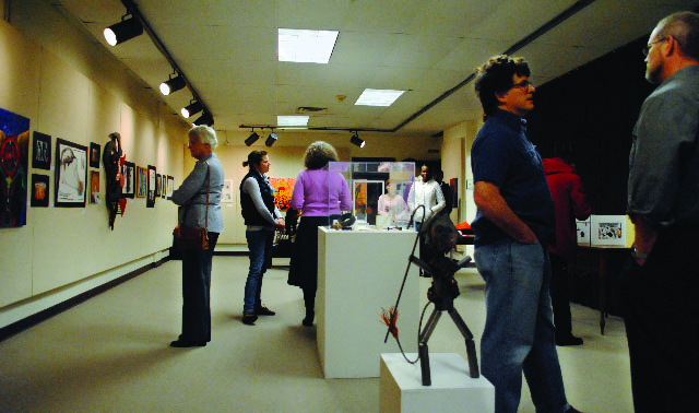 """Students and staff talk and enjoy the """"Lion and Lamb"""" student art exhibit in the Good Library Gallery"""