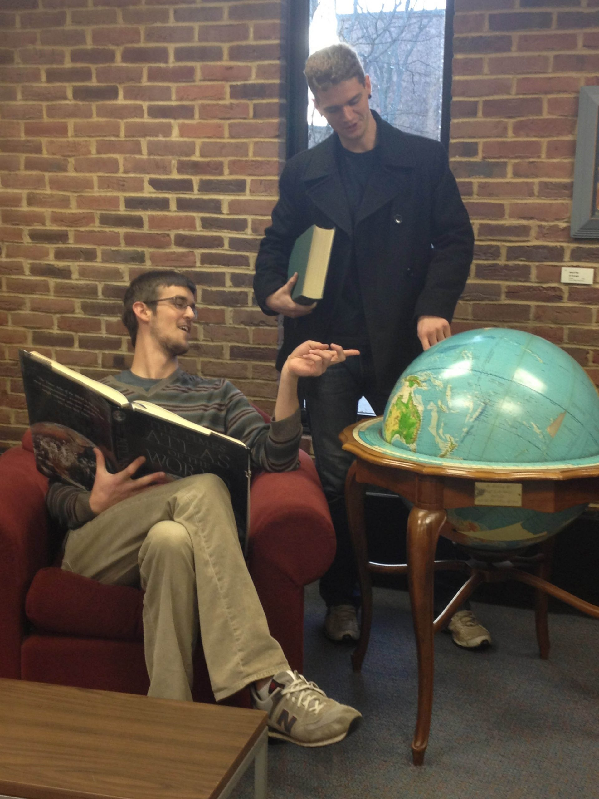 Funnies editors John and Brian point at a large globe in the Good Library