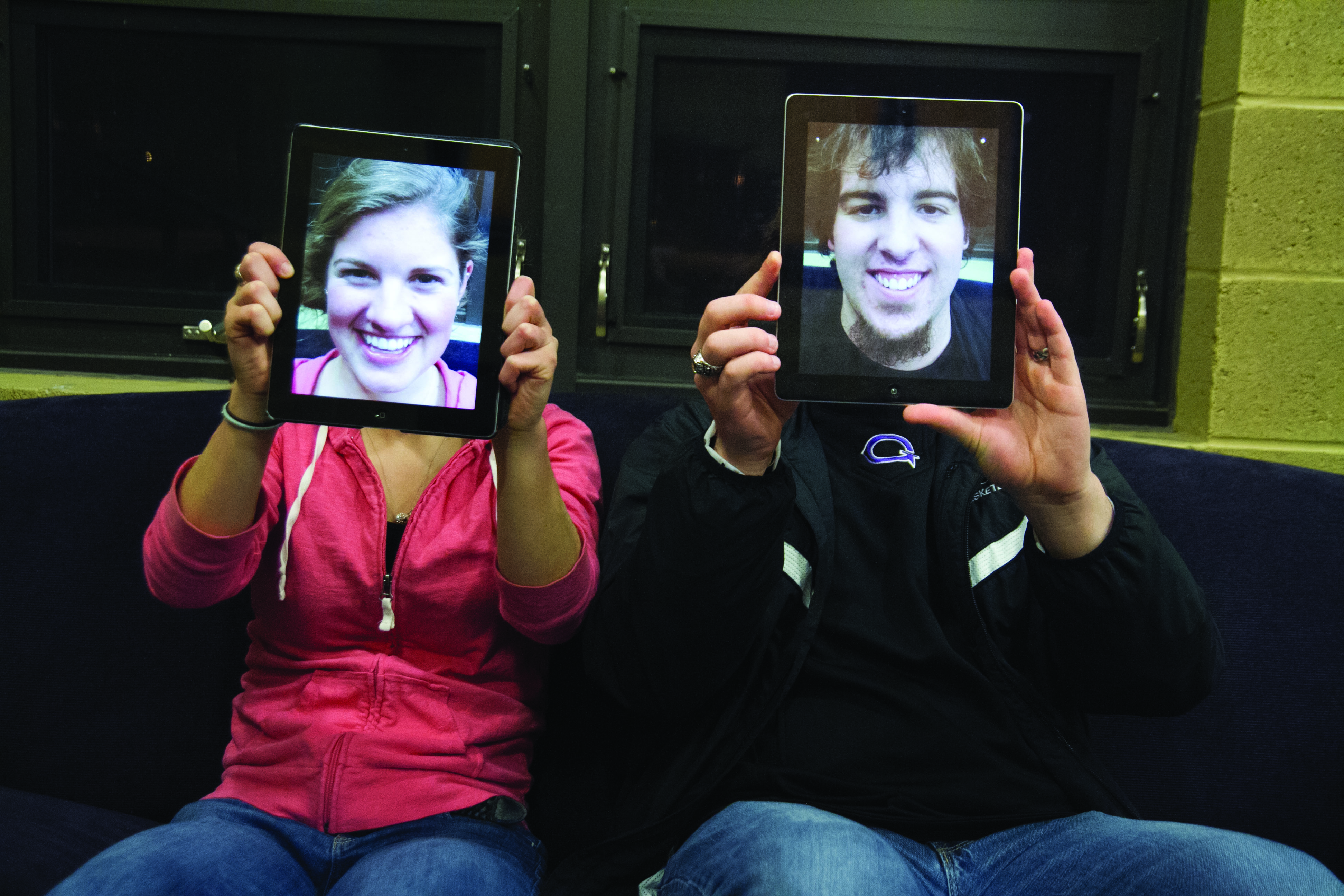 Two students cover their faces with pictures of themselves on their iPads