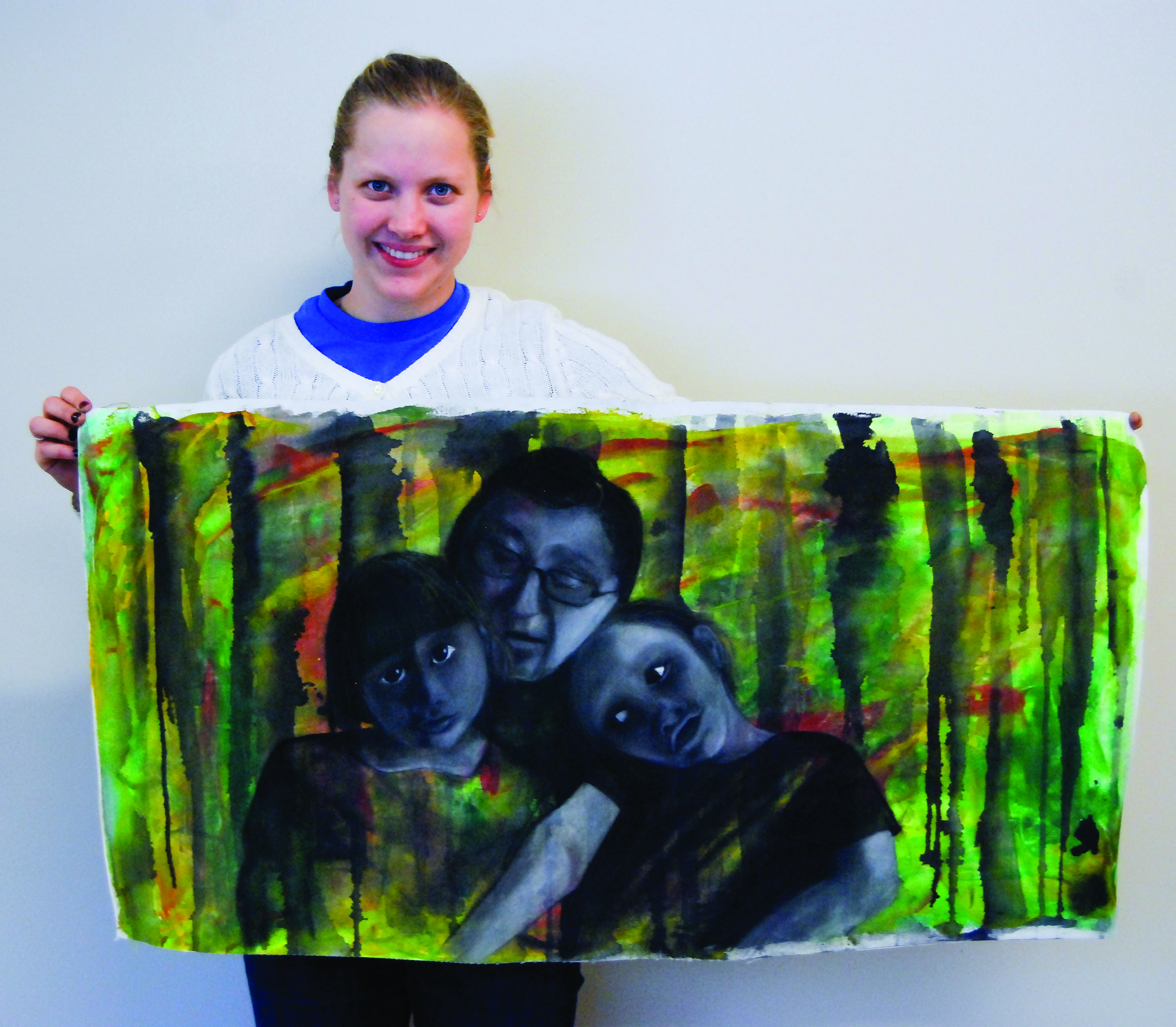 Laurel Woodward holds up one of her paintings