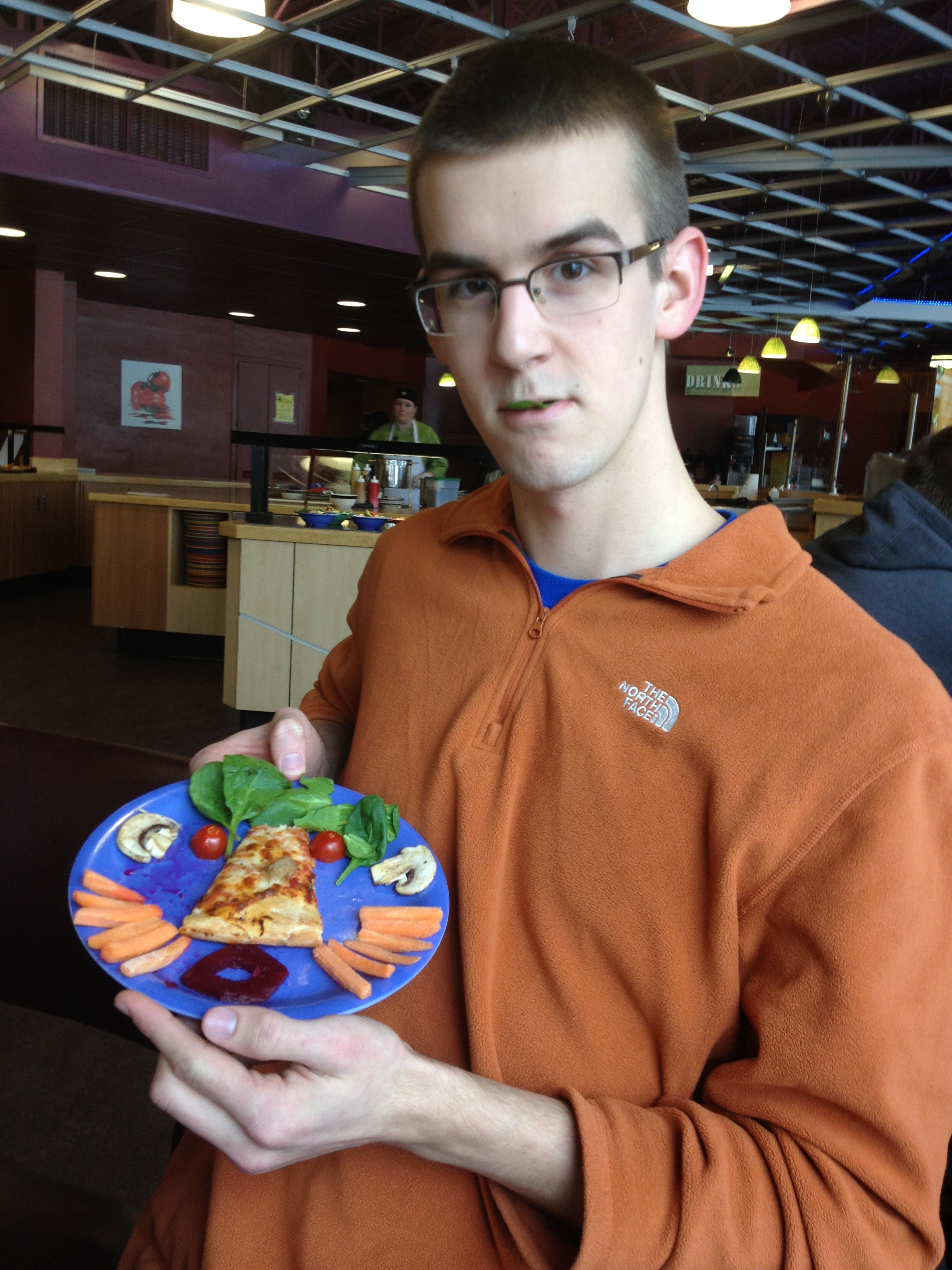 John Miller poses with a plate of food that he has arranged to resemble a face