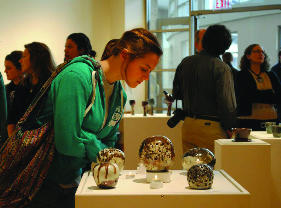A student looks at some of the ceramics on display in the Hershberger Art Gallery