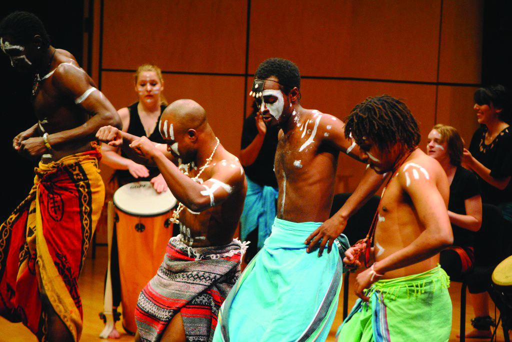 International students dance and play drums on the Sauder Concert Hall stage