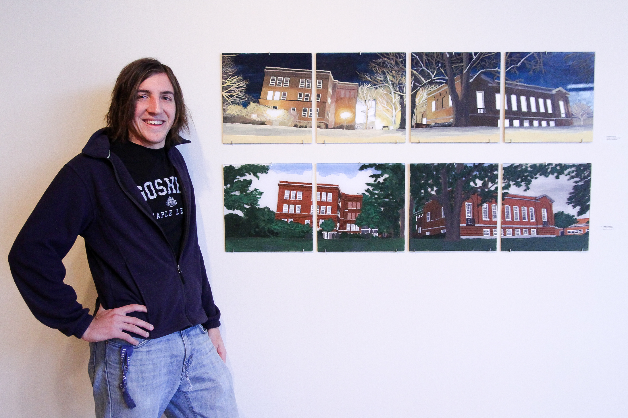 Daniel Buschert poses with some of his drawings of campus locations