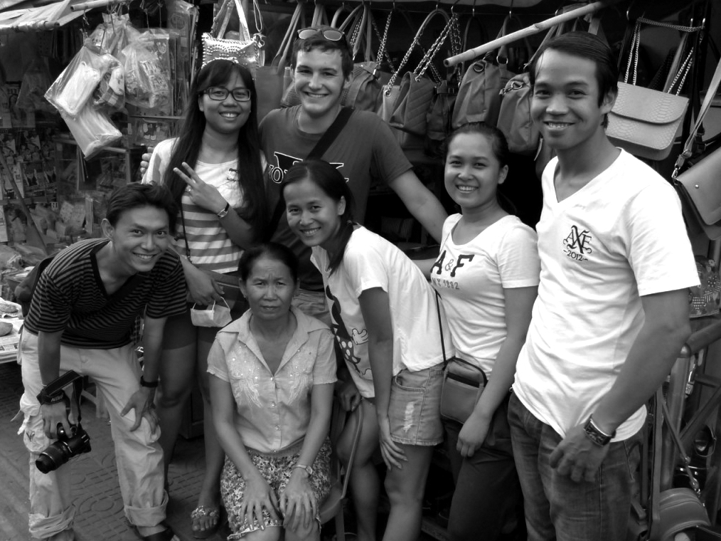 Black and white image of Brett Conrad and his Cambodian host family