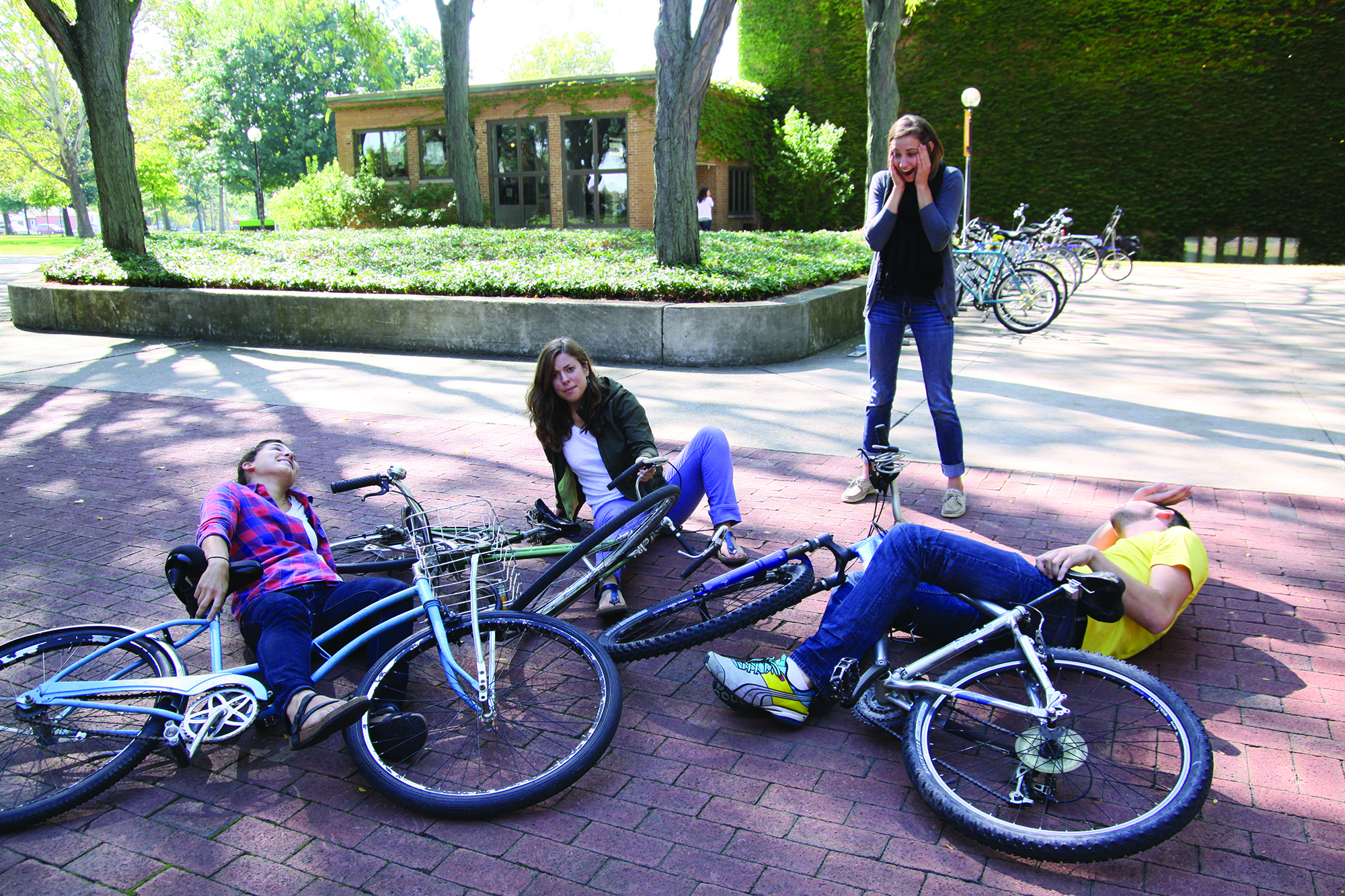 Three students are involved in a bike crash in Schrock Plaza while another student looks on in horror