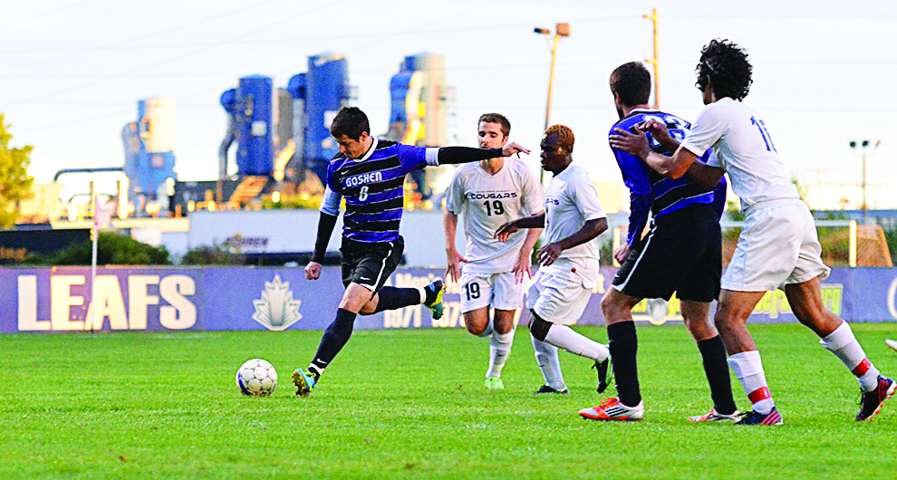 Andres Garcia fends off three opposing players to pass the ball during a home soccer game