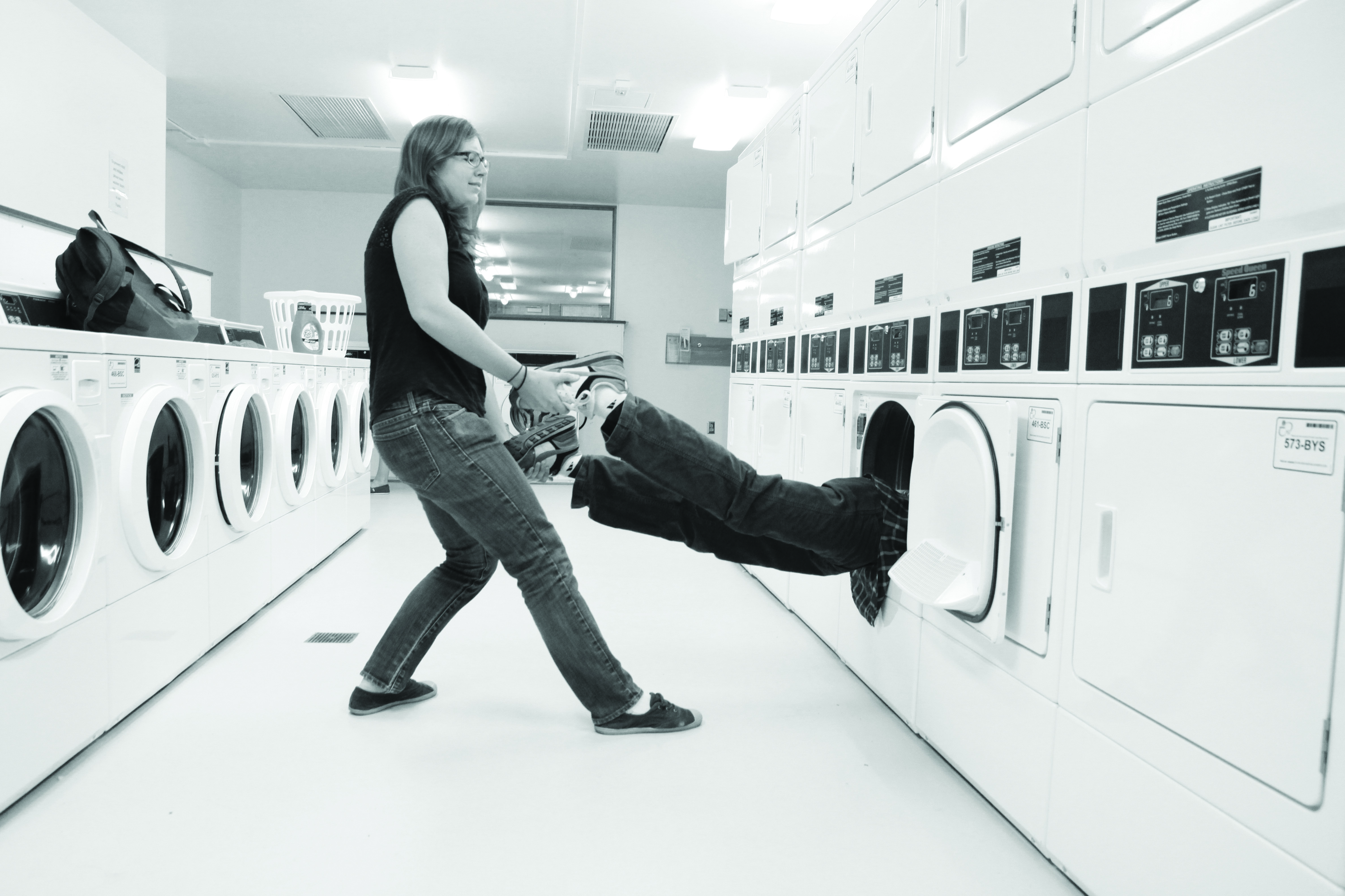 A student pushes another student head first into a washing machine