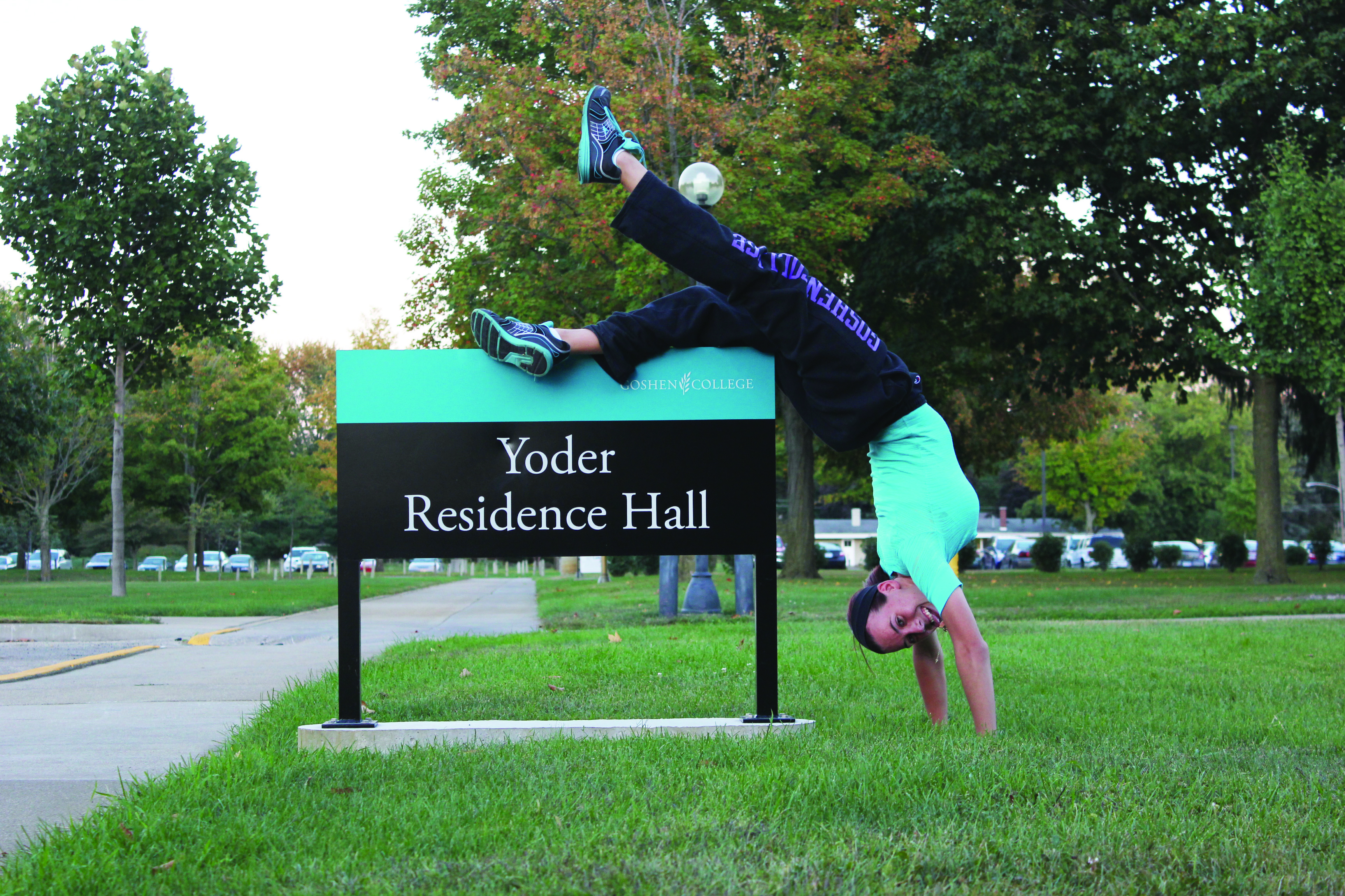Morgan Owens wears a green shirt and does a handstand next to the matching green Yoder Residence Hall sign