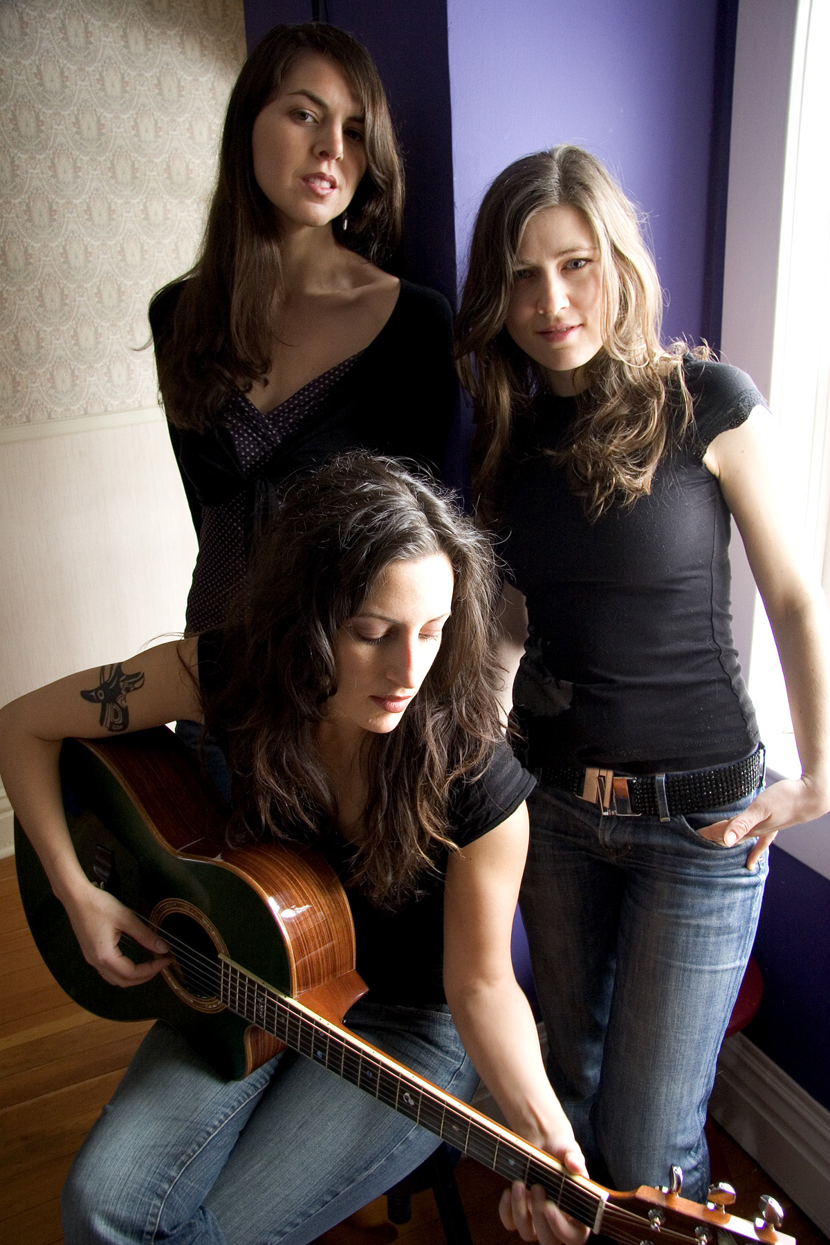 The Wailin' Jennies pose for a picture with a guitar