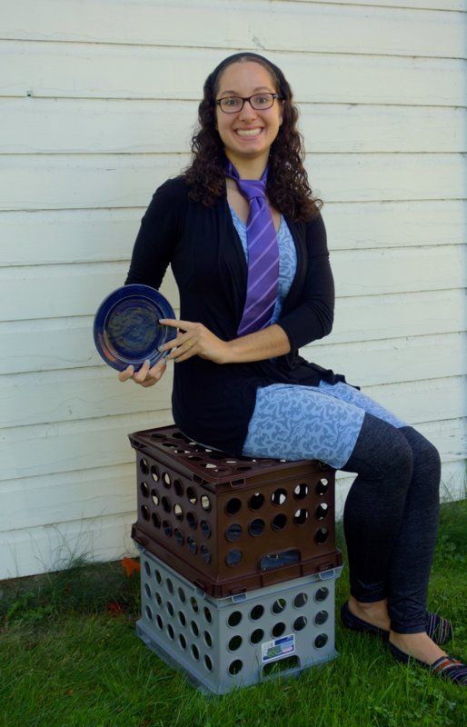 Maria Jantz wears a purple tie and plays with plates and crates