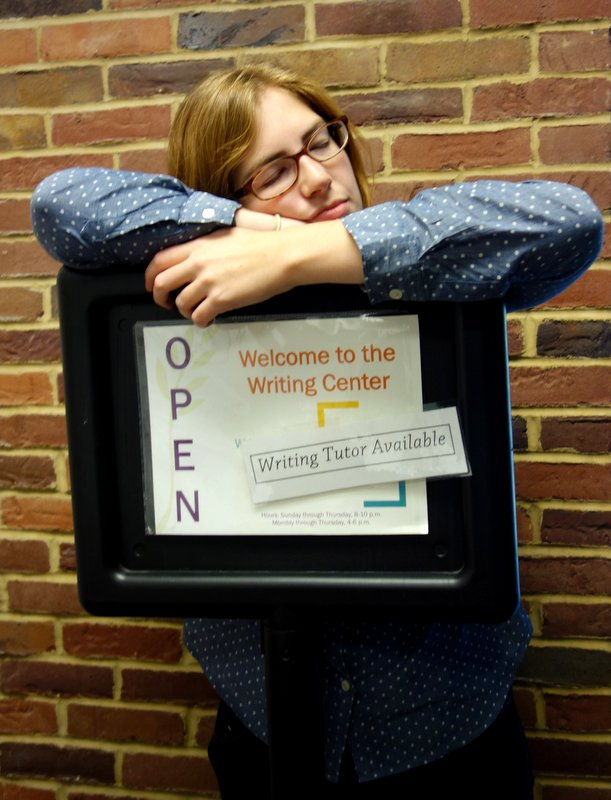 """Kate Yoder takes a nap on the """"Writing Tutor"""" sign in the Good Library"""