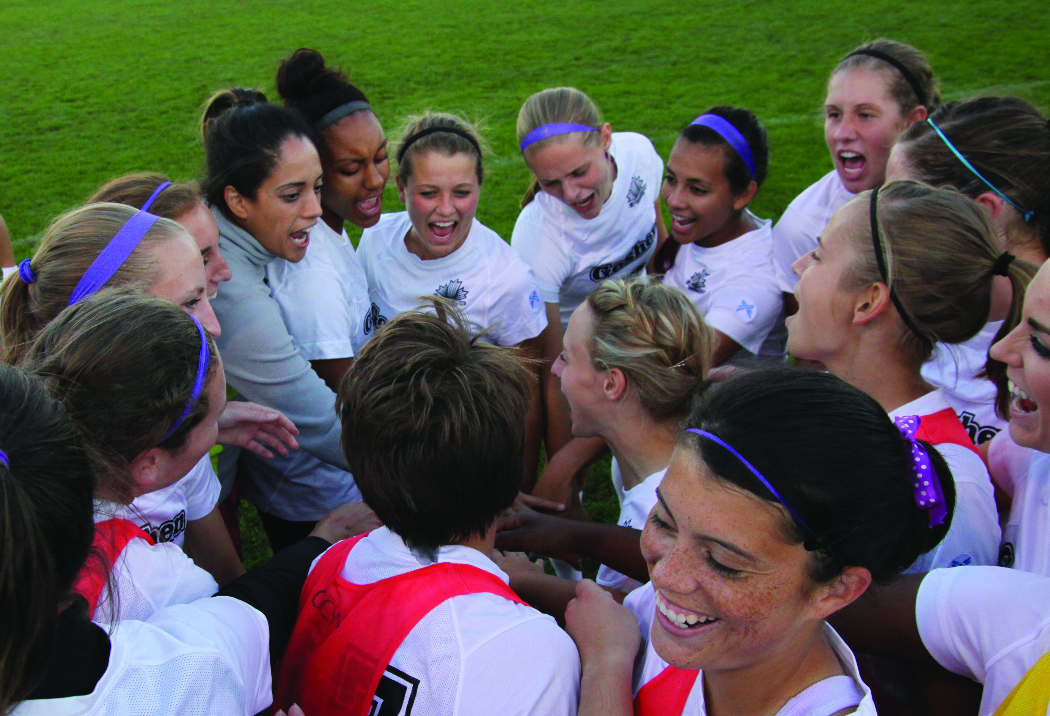 The women's soccer team enjoys a group embrace before a game