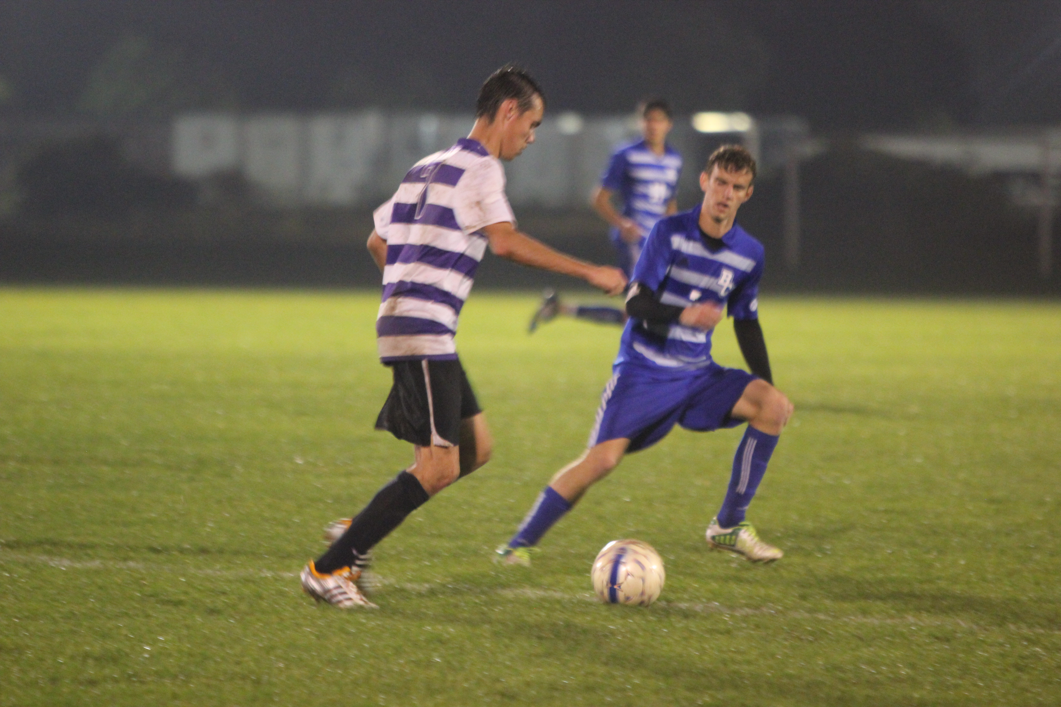 Chris Vendrely fends off an opponent as he dribbles the ball down the field during a soccer game