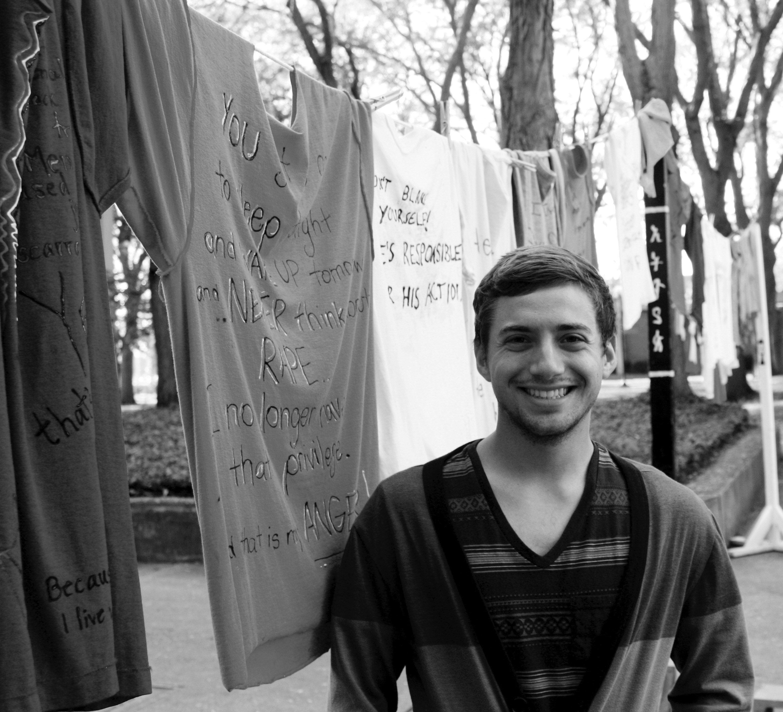 Stefan stands by the T-shirts hanging on a clothesline in Schrock Plaza for the PIN clothesline project