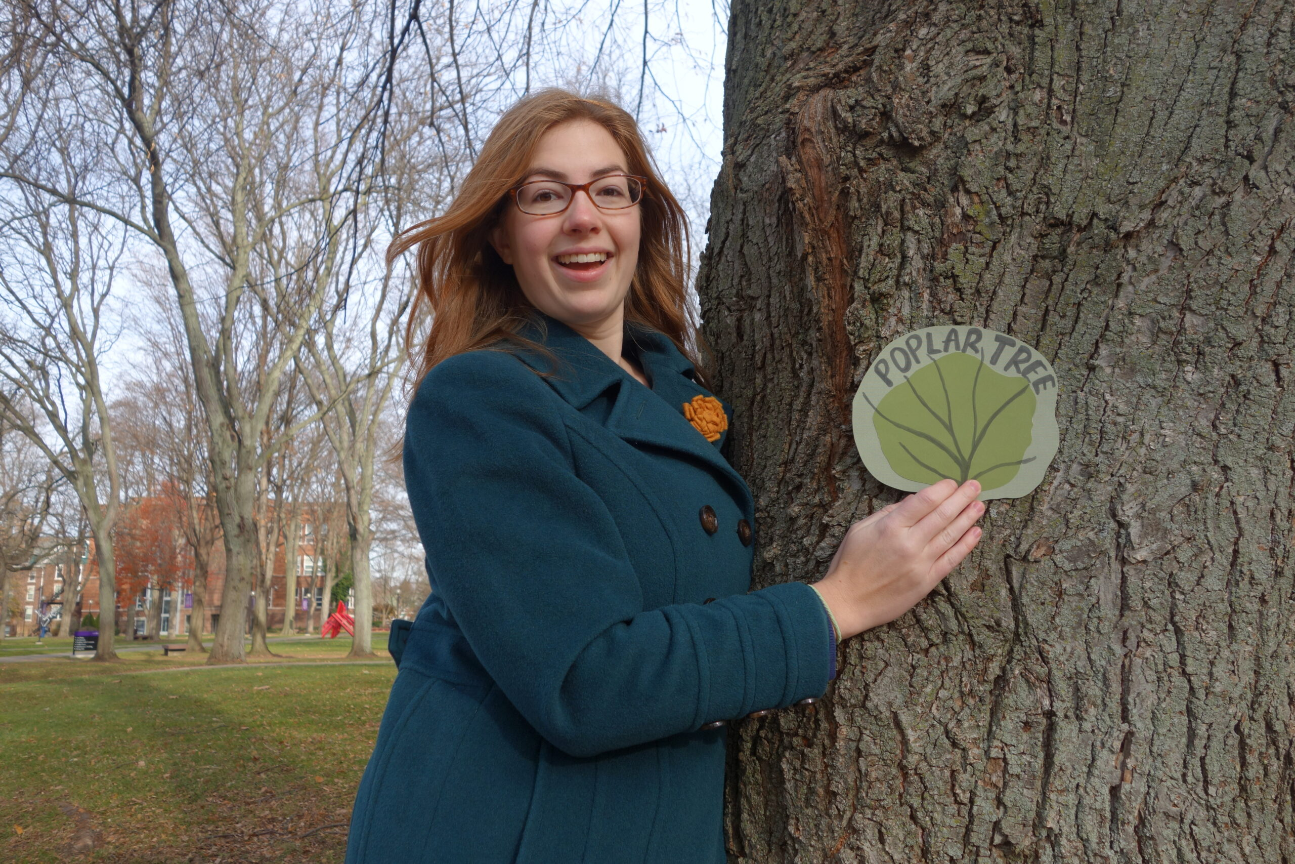 """Kate Yoder poses next to a tree labeled """"Poplar Tree"""""""