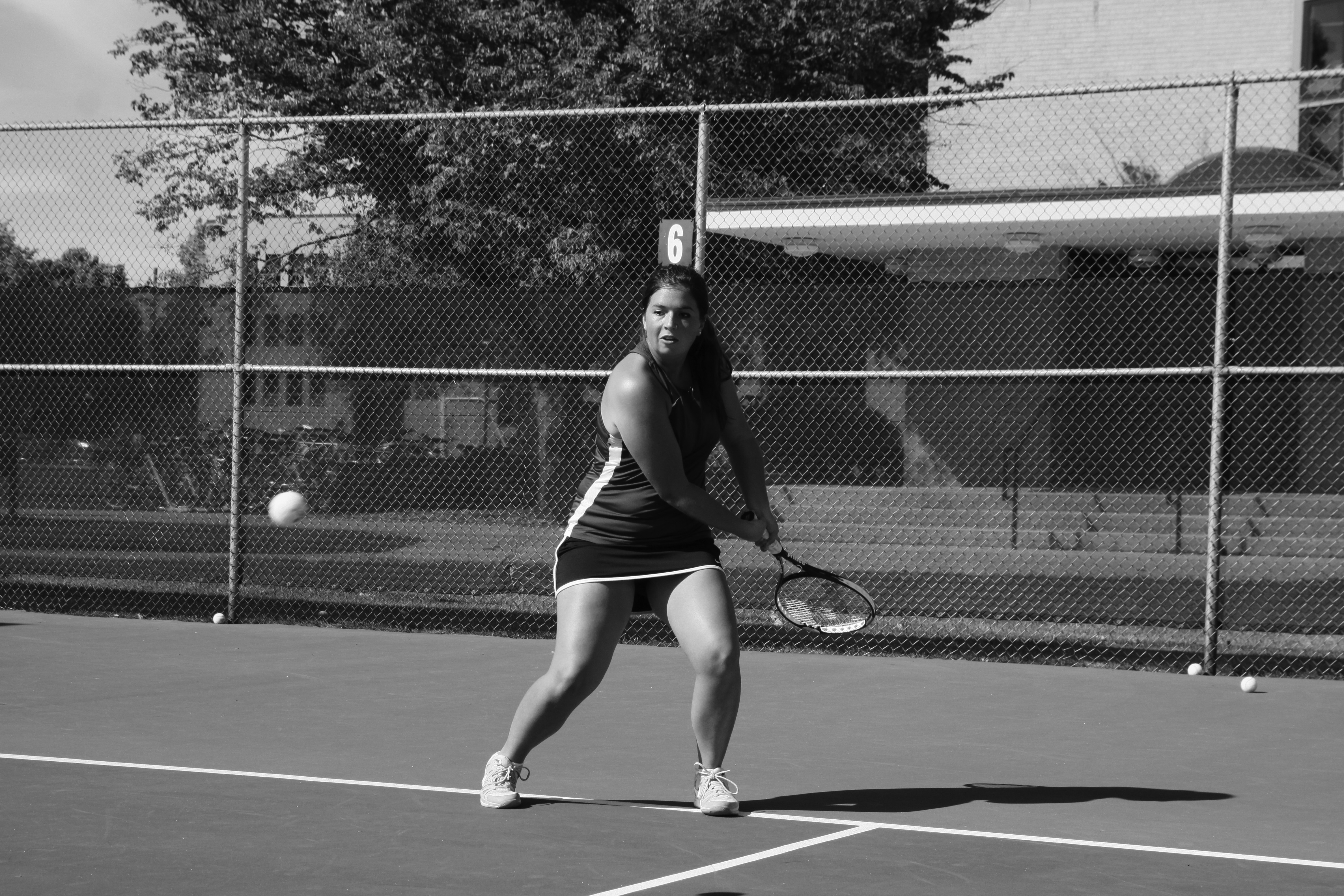 Black and white image of Maria Thomas preparing to hit the ball in a tennis match