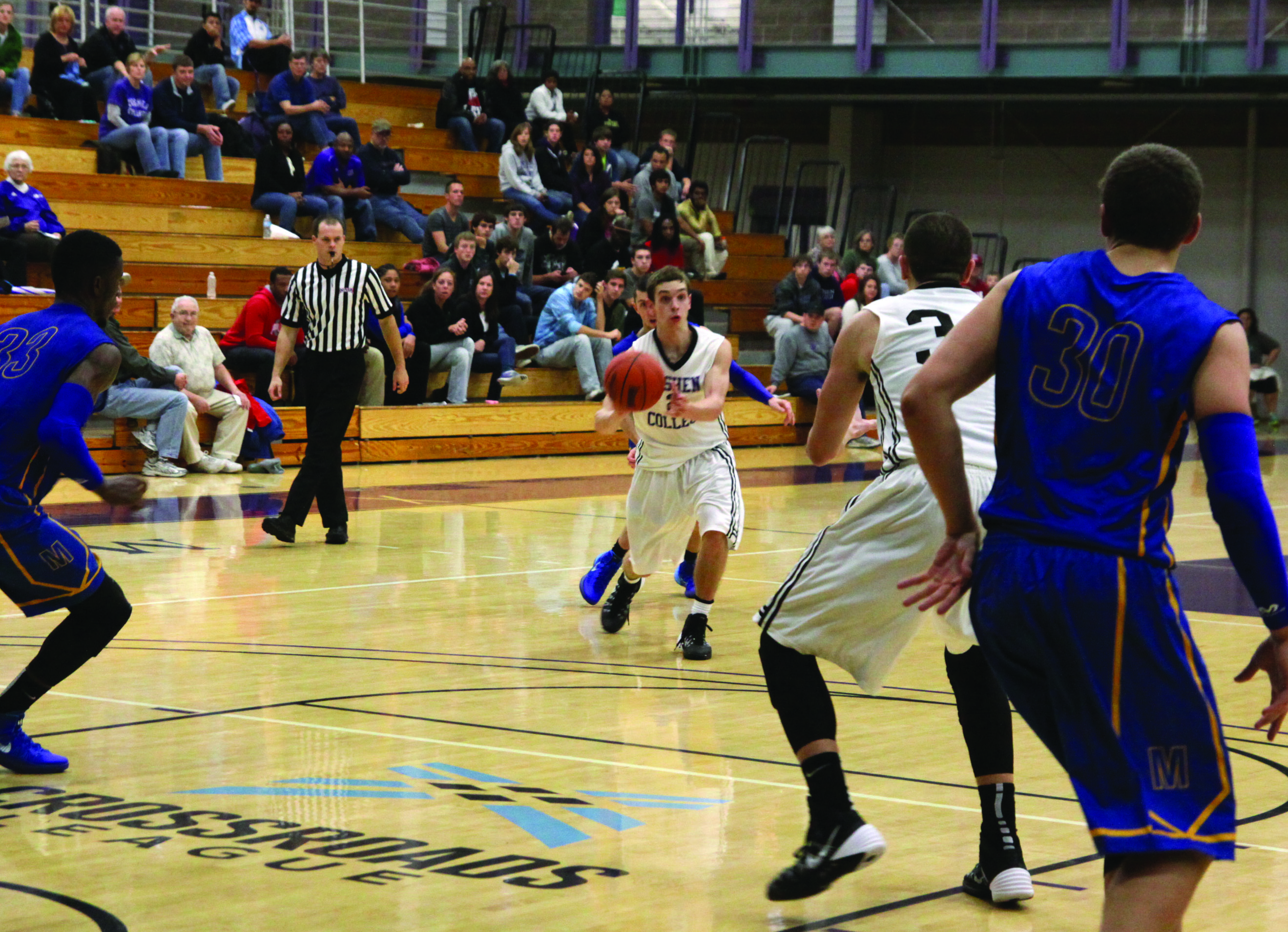 A player on the Goshen men's basketball team prepares to throw the ball in a game. Another Goshen player and two opposing players are in the foreground of the shot, while spectators can be seen on bleachers in the background