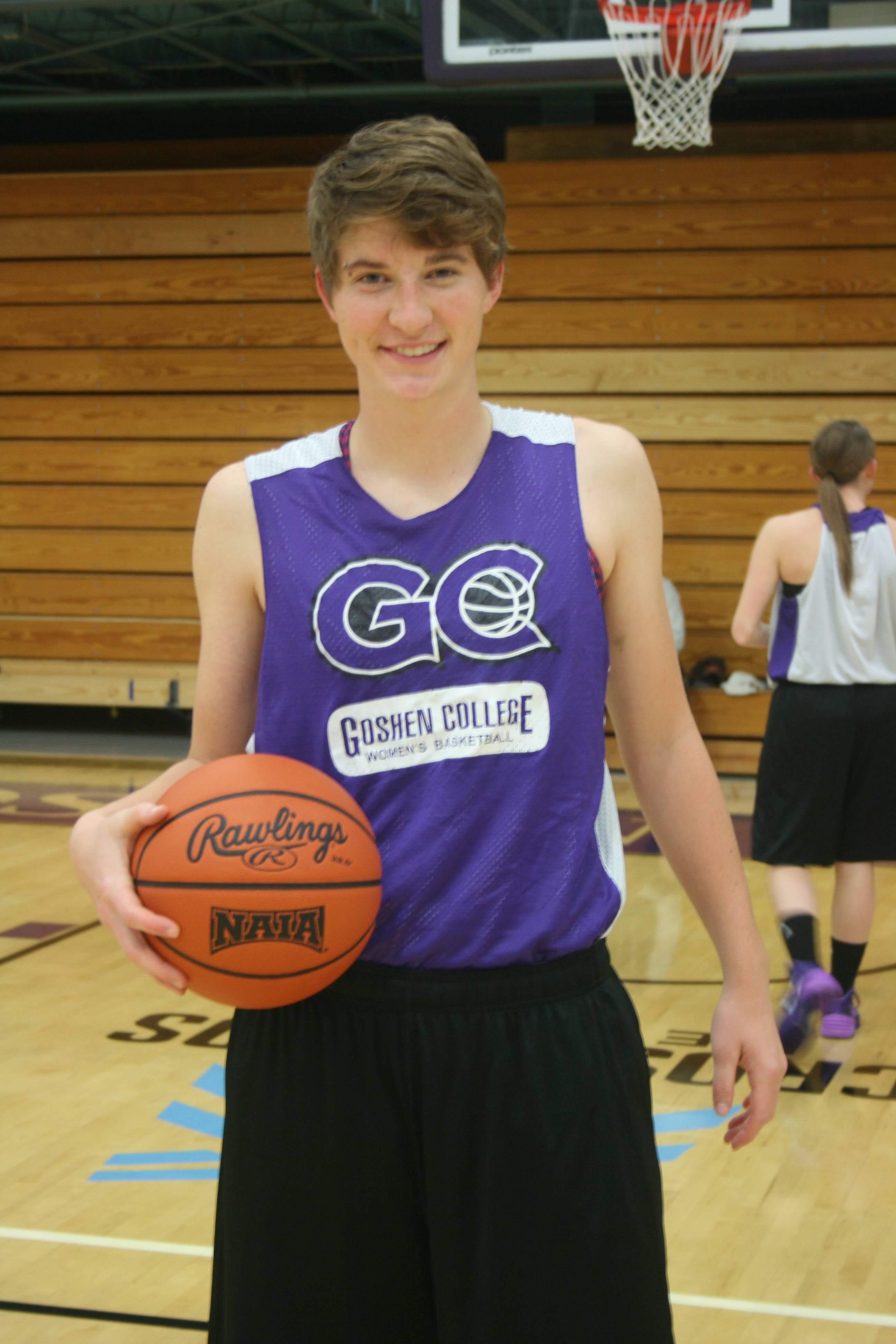 Natalie Thorne poses for a picture in her Goshen jersey, holding a basketball in one hand