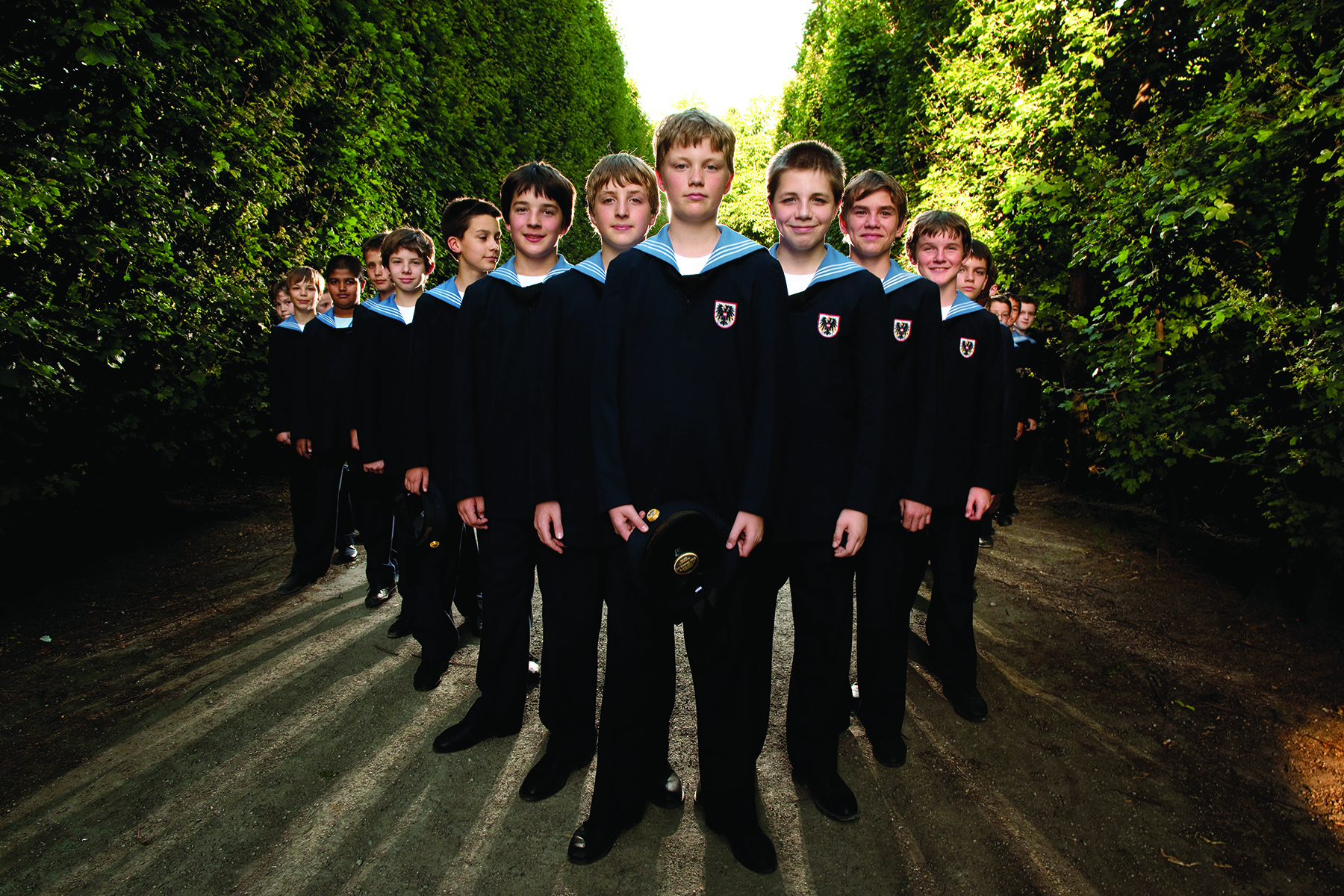 Members of the Vienna Boys Choir stand in a triangle formation for a photo