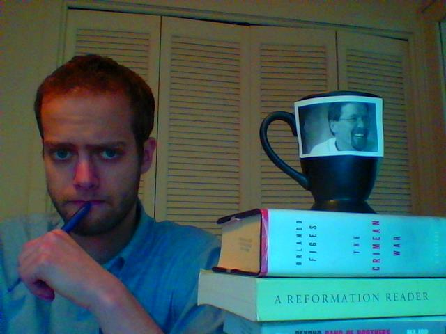 Nathan Geiser makes a sad face for the camera next to a mug with John Roth's picture on it