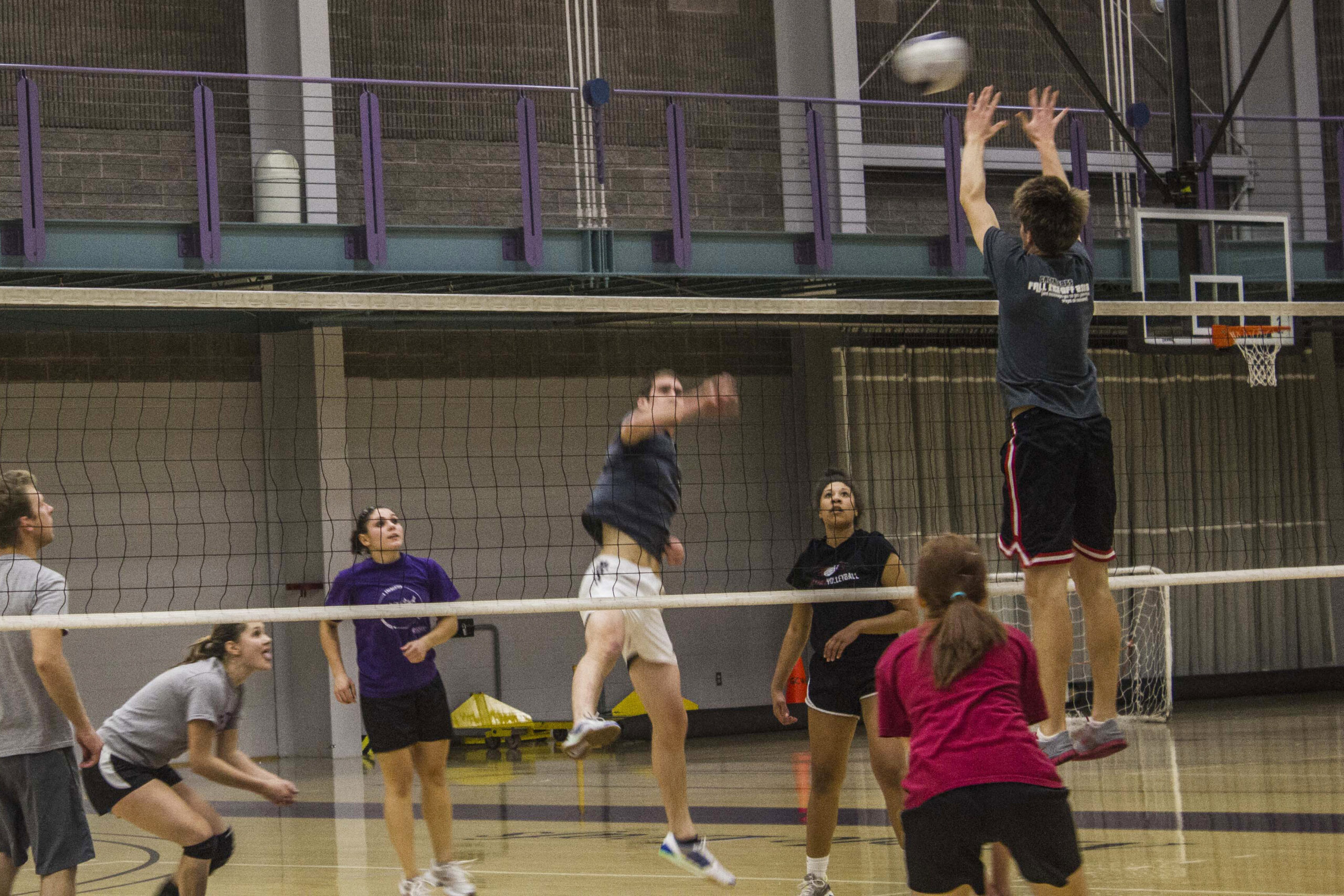 A player from the Compassionate Killers spikes the ball to Block Market during an intramural volleyball game