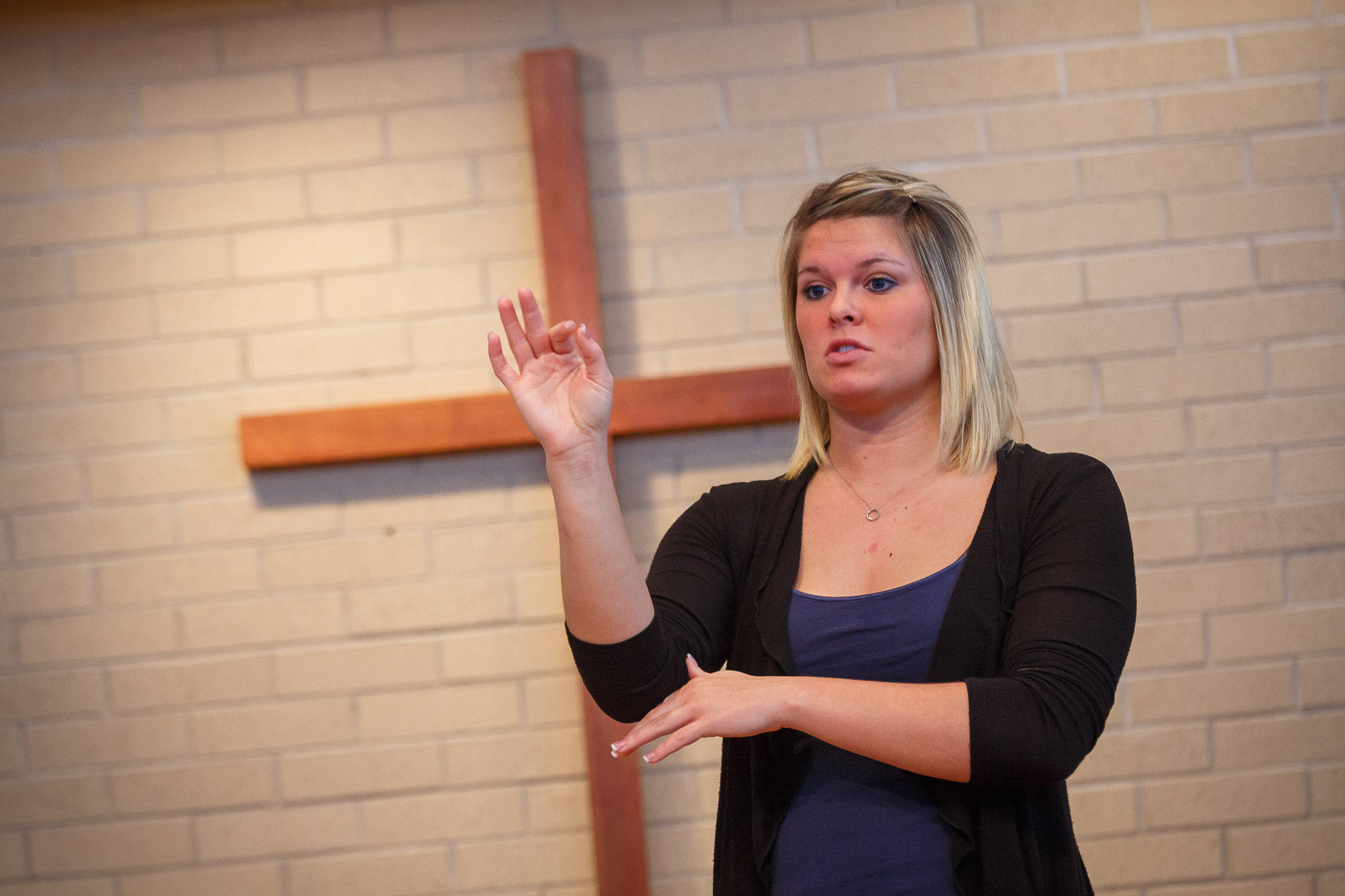 An ASL student interprets in the Church-Chapel, a large wooden cross in the background