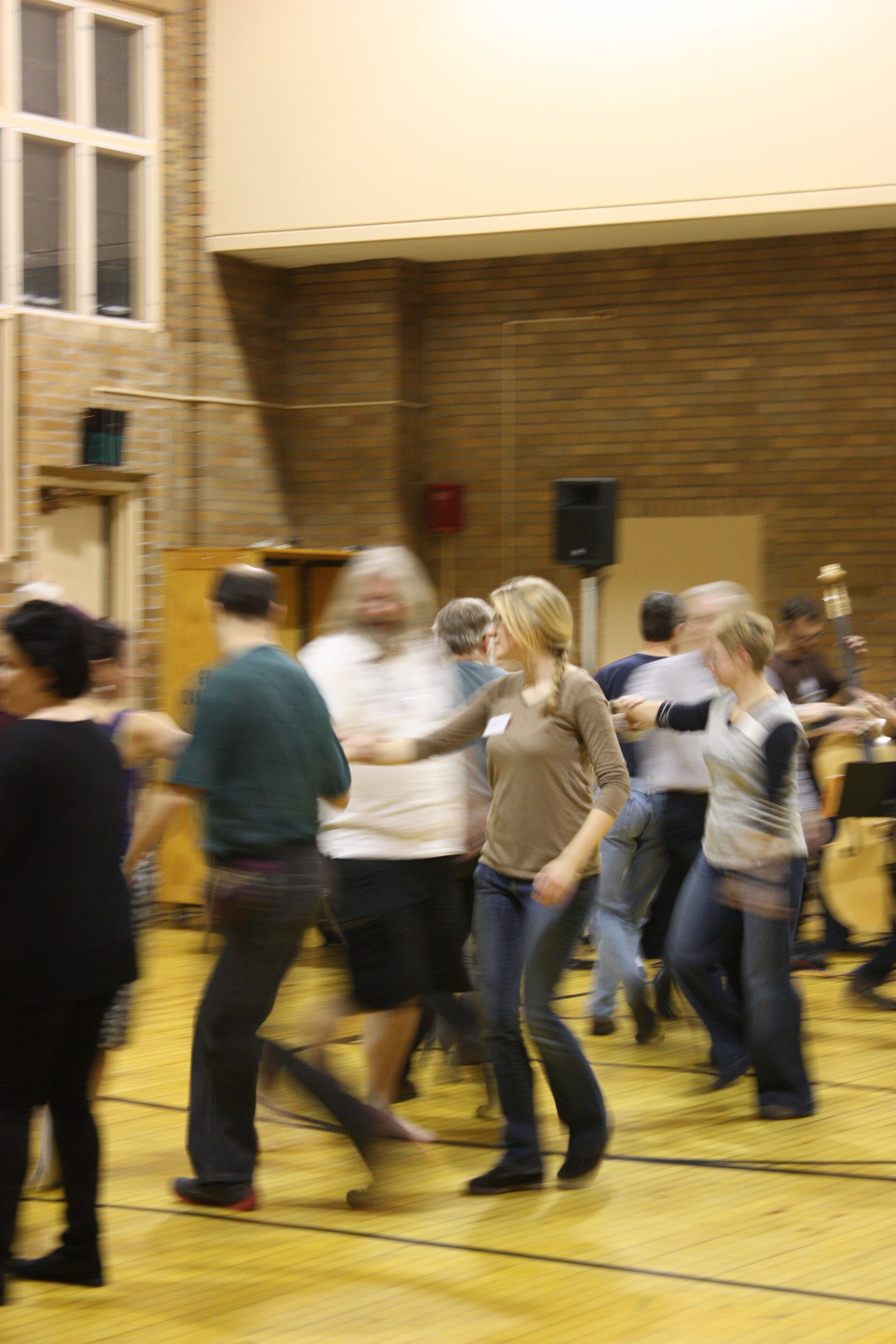 A large group of people participate in the monthly Goshen contra dance; Kate Friesen is clear, while the other dancers are blurry