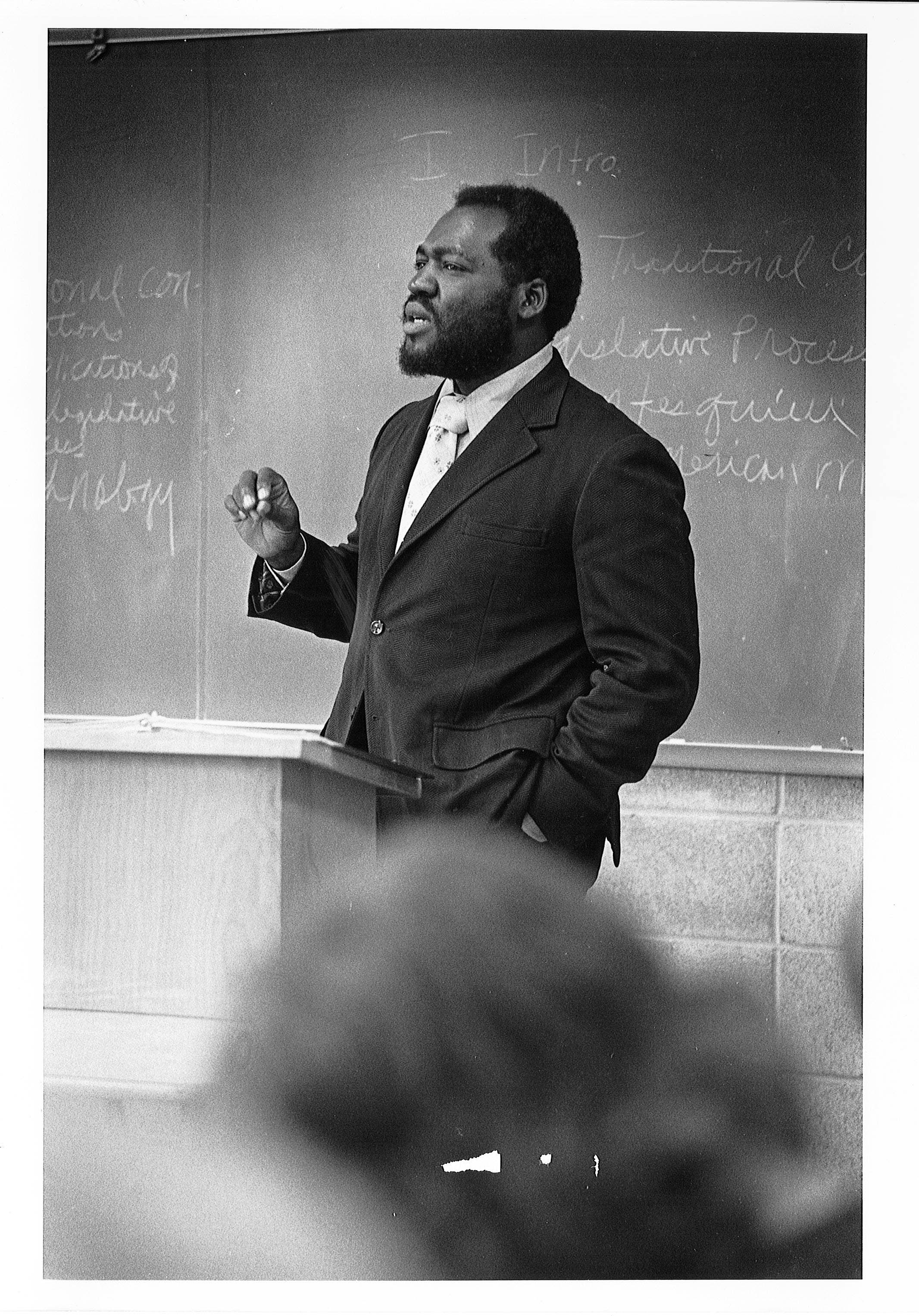 Black and white image of Lee Roy Berry lecturing in front of a classroom chalkboard