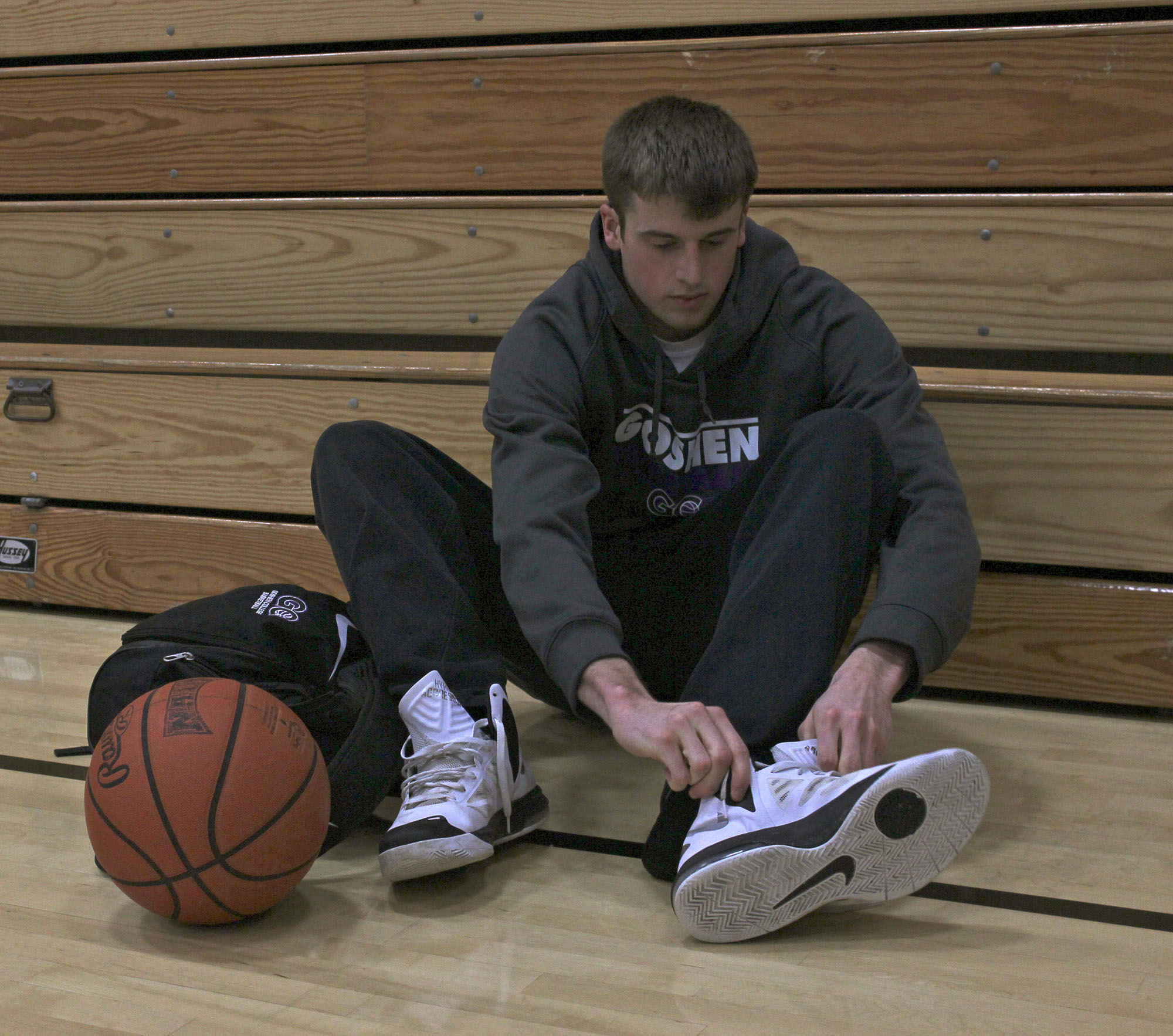 basketball player putting shoes on
