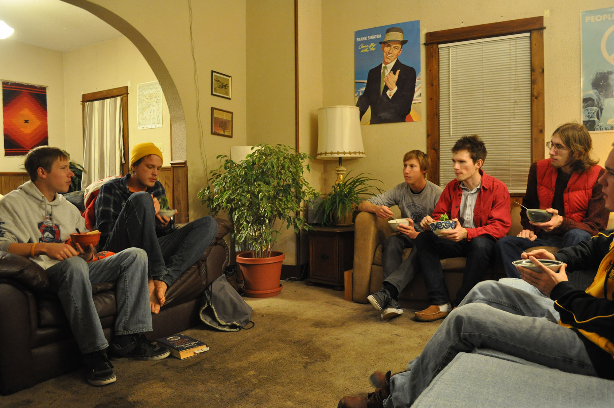 Members of the Social Reform Club sit around a small living room and converse