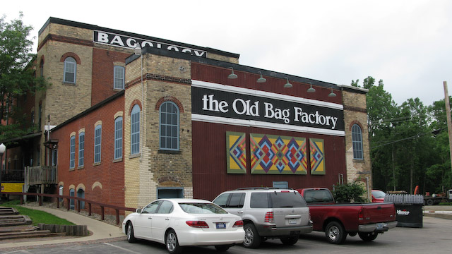 """Image of the large, brick Old Bag Factory building and its parking lot. The building features a brightly colored mosaic and a black and white sign reading """"The Old Bag Factory"""""""